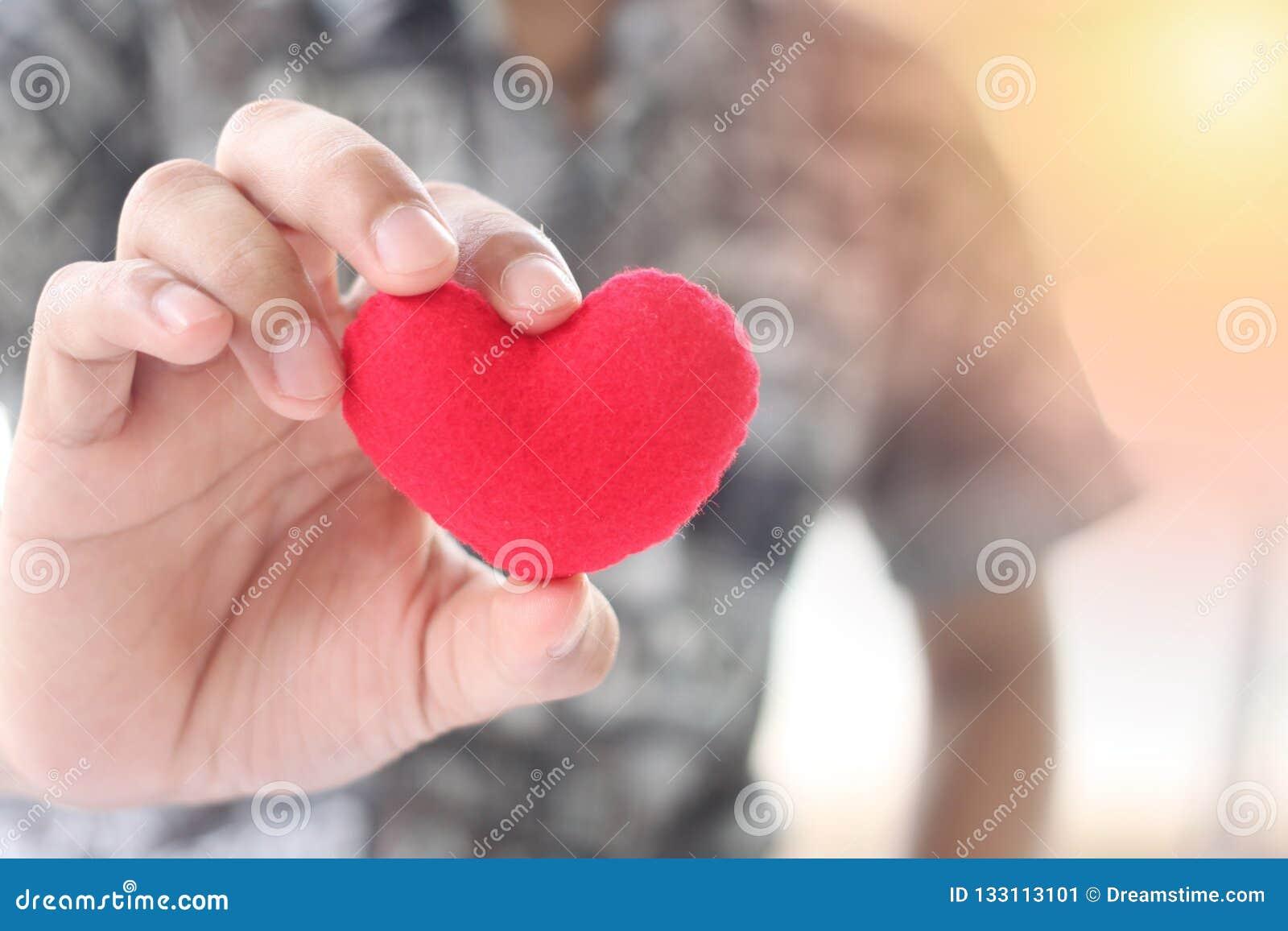 Ένα άτομο που κρατά μια κόκκινη καρδιά στο χέρι του