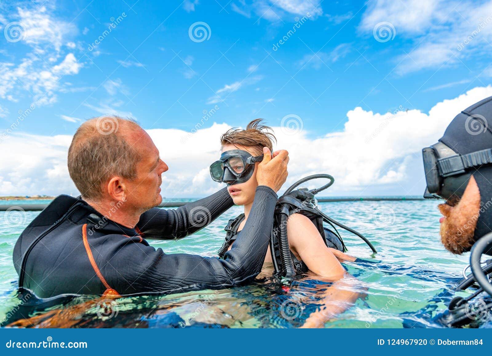 Ένα άτομο σε ένα κοστούμι για την κατάδυση προετοιμάζει ένα αγόρι για να βουτήξει