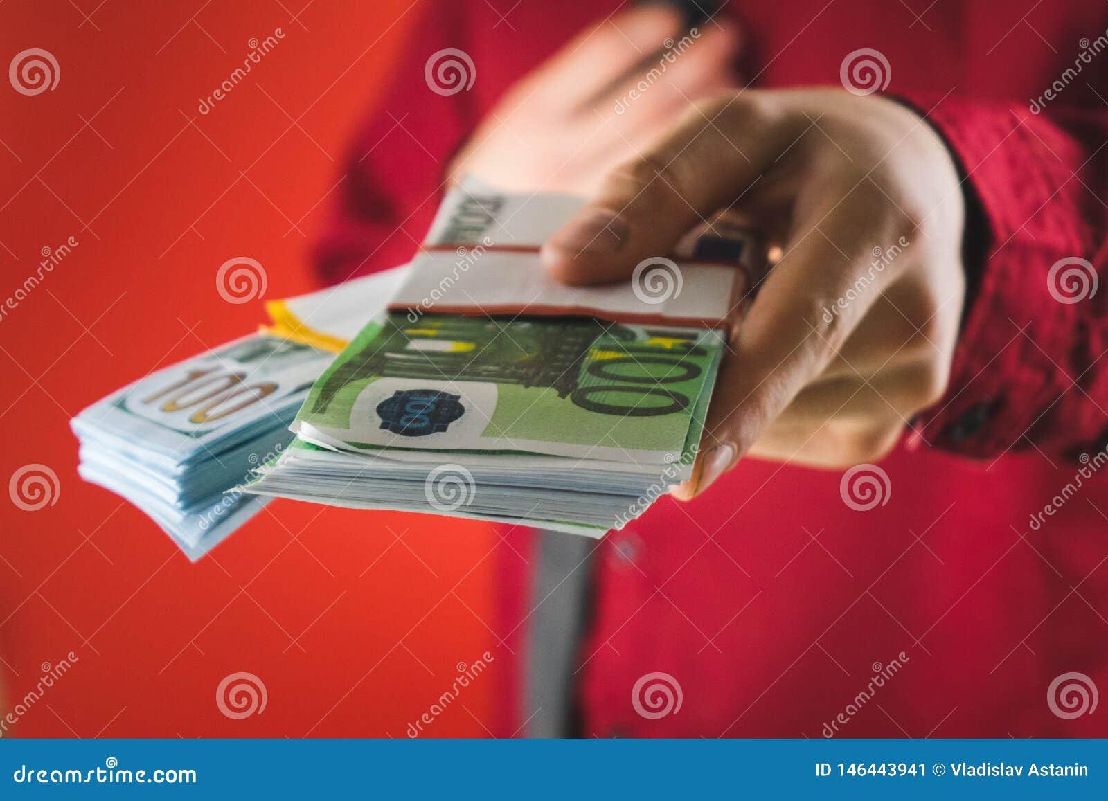 ένα άτομο σε ένα κόκκινο πουκάμισο με μια κάρτα κρατά στο χέρι του ένα wad των λογαριασμών σε ένα κόκκινο υπόβαθρο
