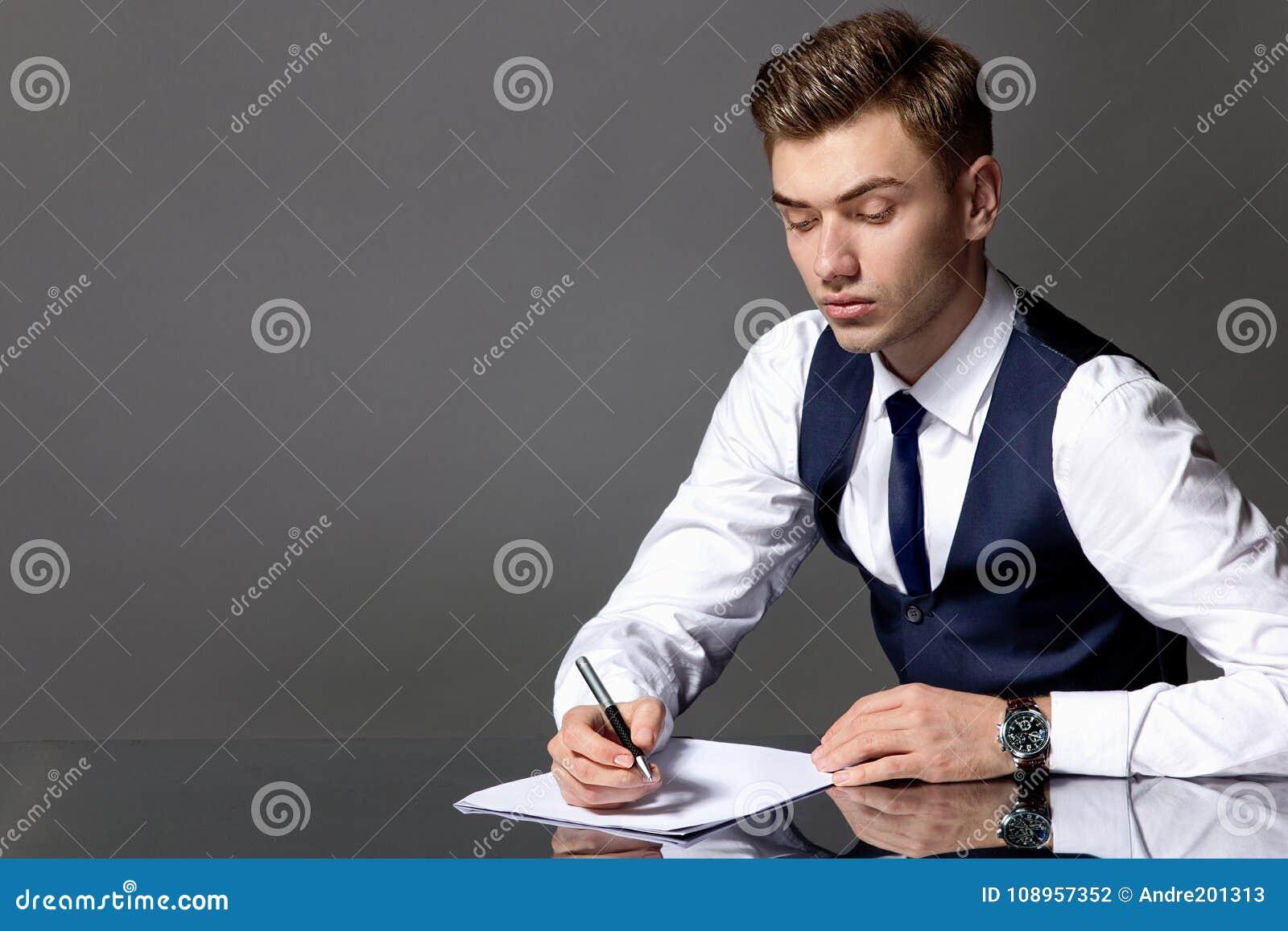 Ένα άτομο σε ένα μπλε γιλέκο και έναν δεσμό κάθεται σε έναν πίνακα και ένα  γράψιμο ed6b9d8845f