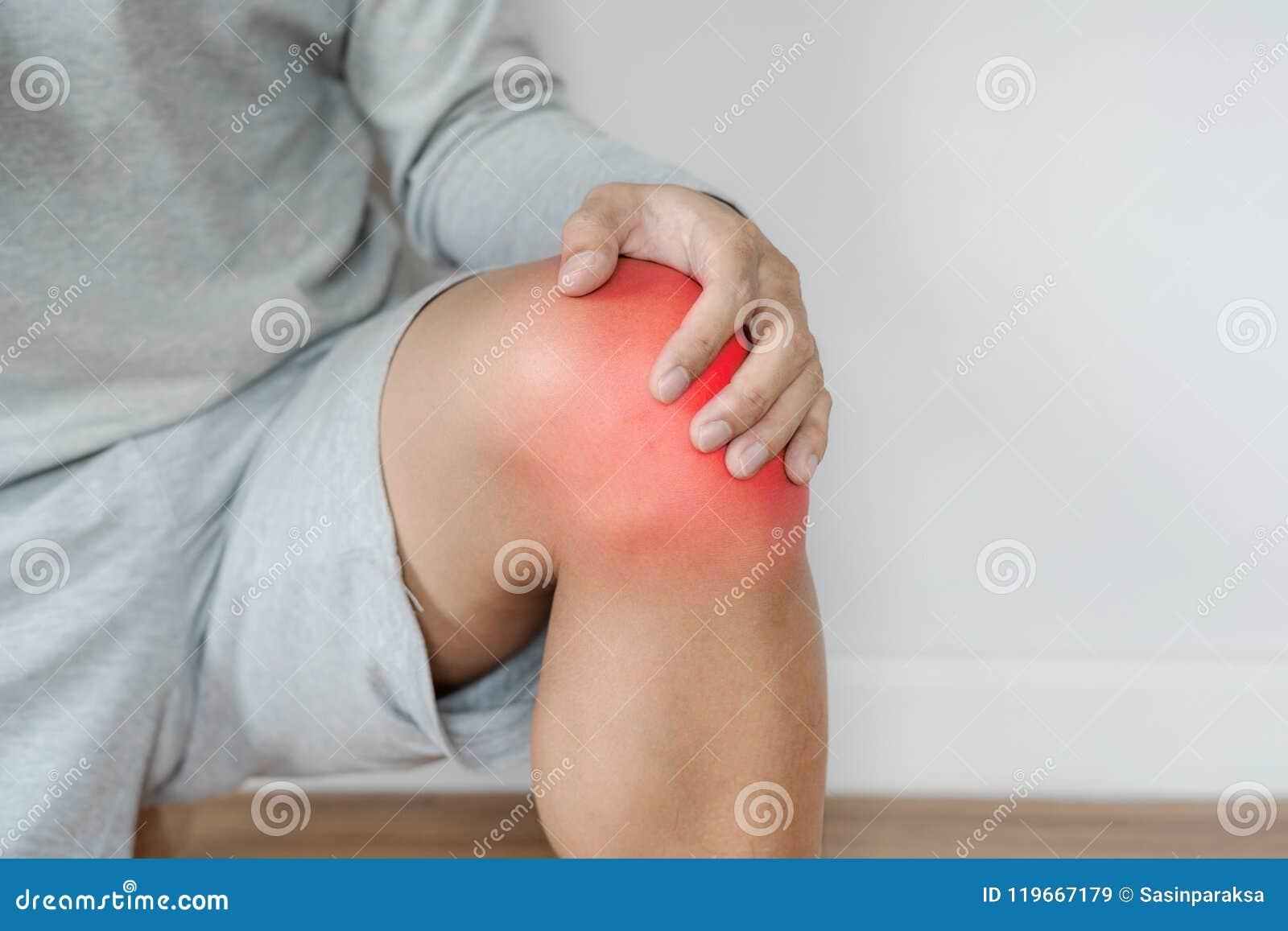 Ένα άτομο σχετικά με το γόνατο με το κόκκινο δίνει έμφαση στην έννοια του γονάτου και του κοινού πόνου