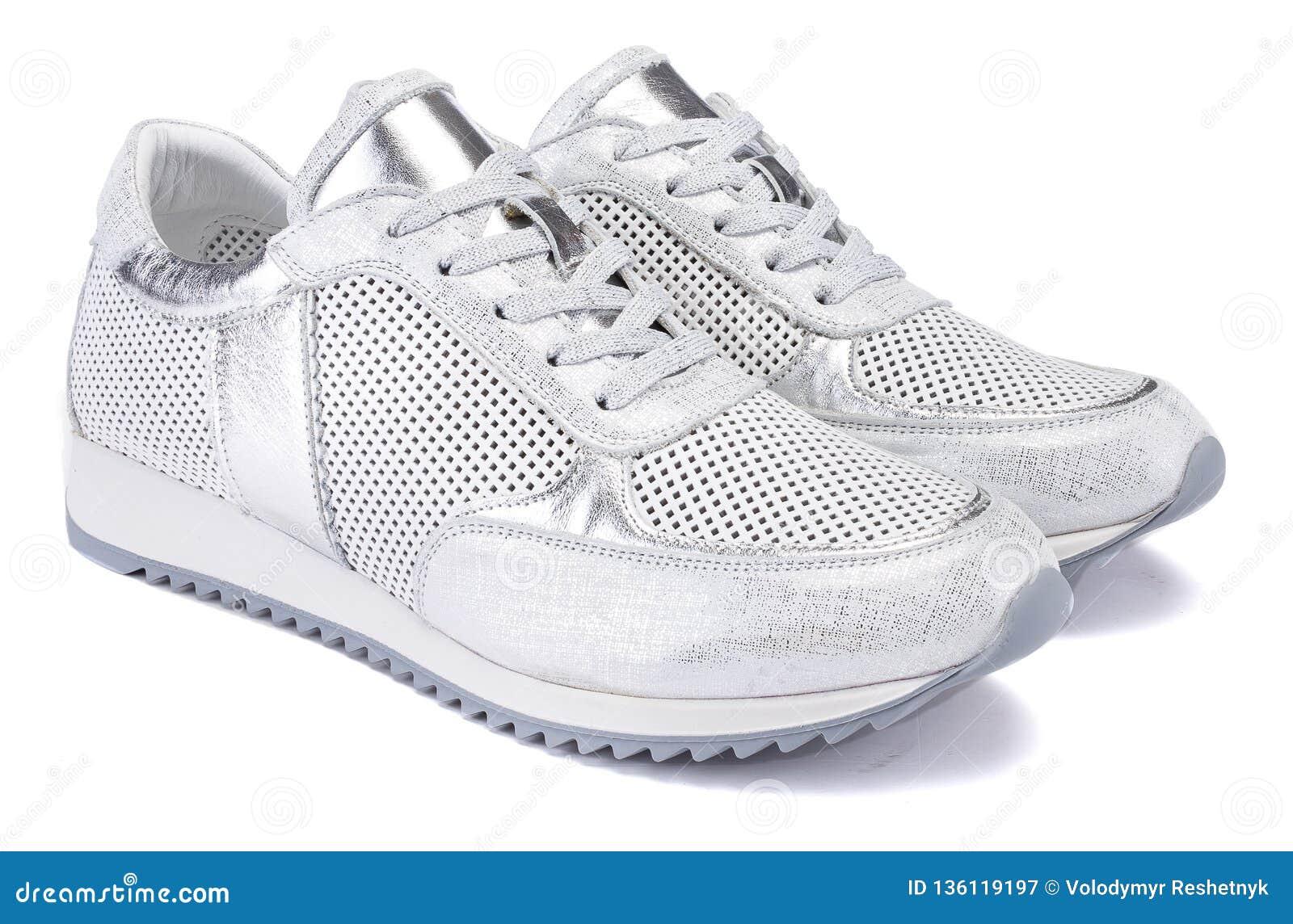 Ένα αθλητικό ενεργό ασημένιο μεταλλικό πάνινο παπούτσι απομονώνει στο άσπρο υπόβαθρο