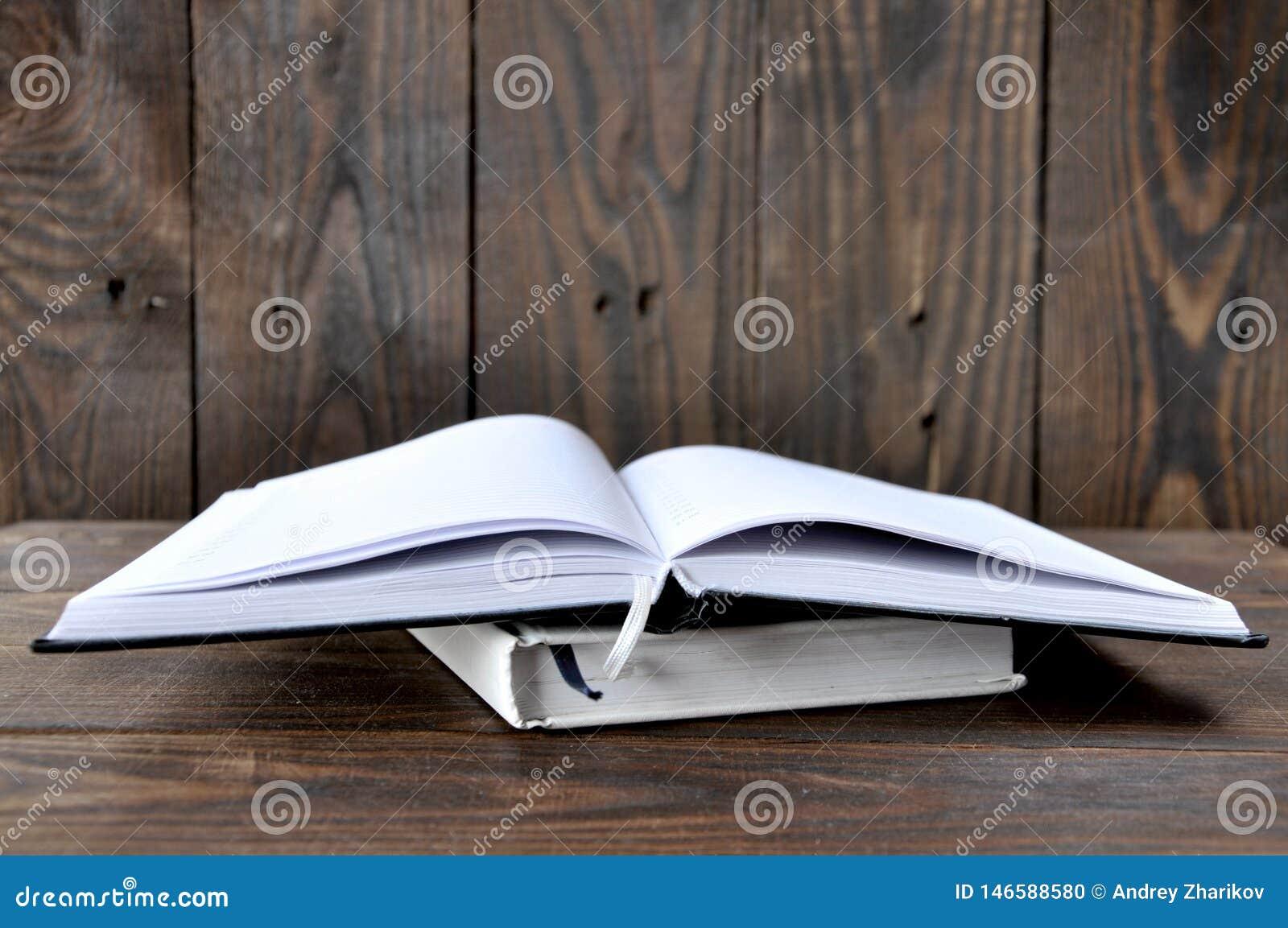 Ένα ανοικτό βιβλίο ή ένα σημειωματάριο βρίσκεται σε έναν ξύλινο πίνακα