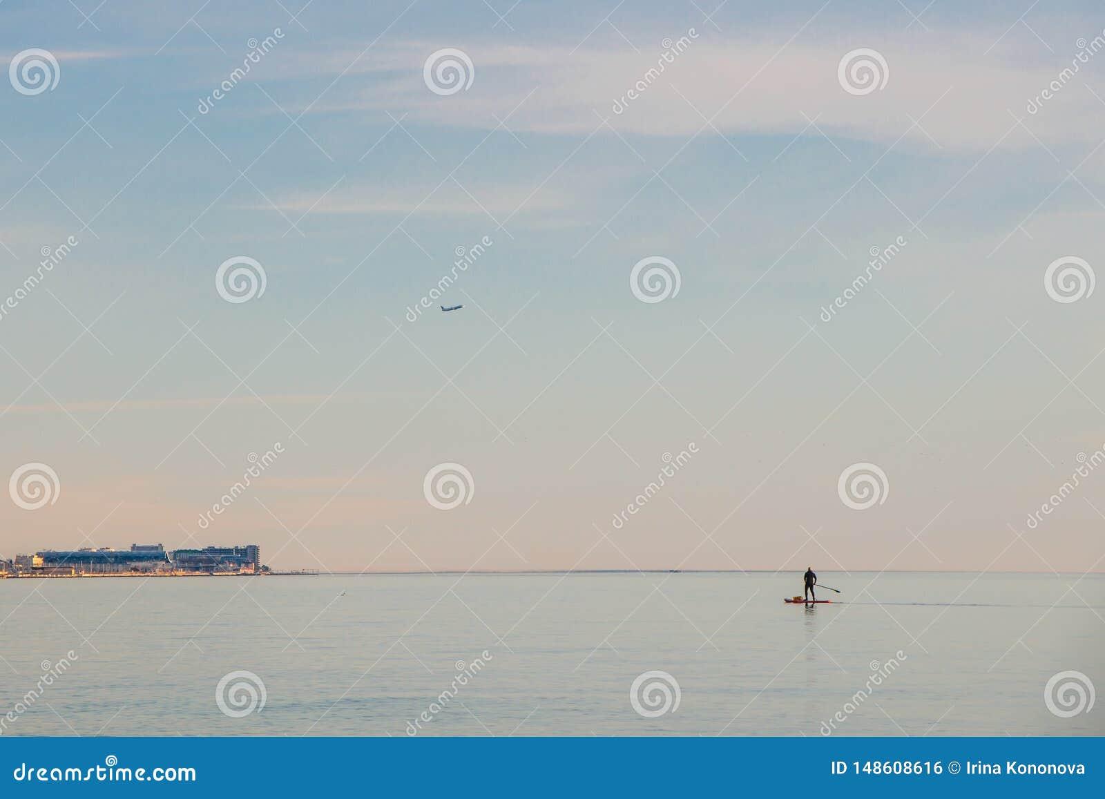 Ένα απομονωμένο άτομο με μια τσάντα που κινείται πέρα από τη θάλασσα σε μια ιστιοσανίδα με ένα κουπί r