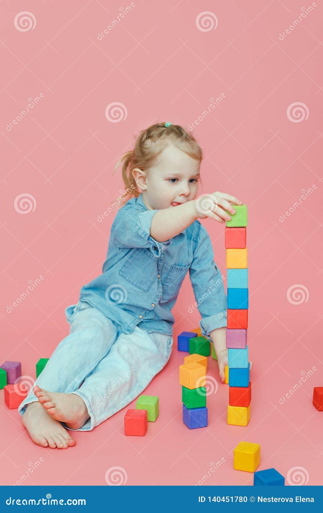 Ένα γοητευτικό μικρό κορίτσι στα ενδύματα τζιν σε ένα ρόδινο υπόβαθρο χτίζει έναν πύργο