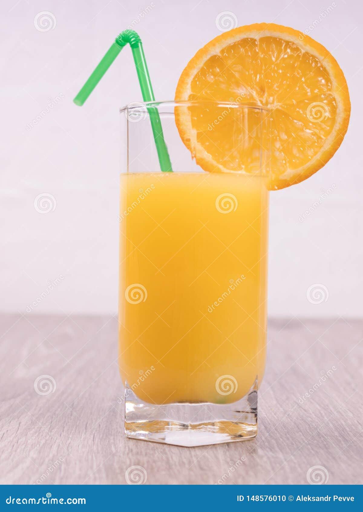 Ένα γυαλί με ένα άχυρο που διακοσμείται με μια φέτα του πορτοκαλιού σε ένα ελαφρύ υπόβαθρο