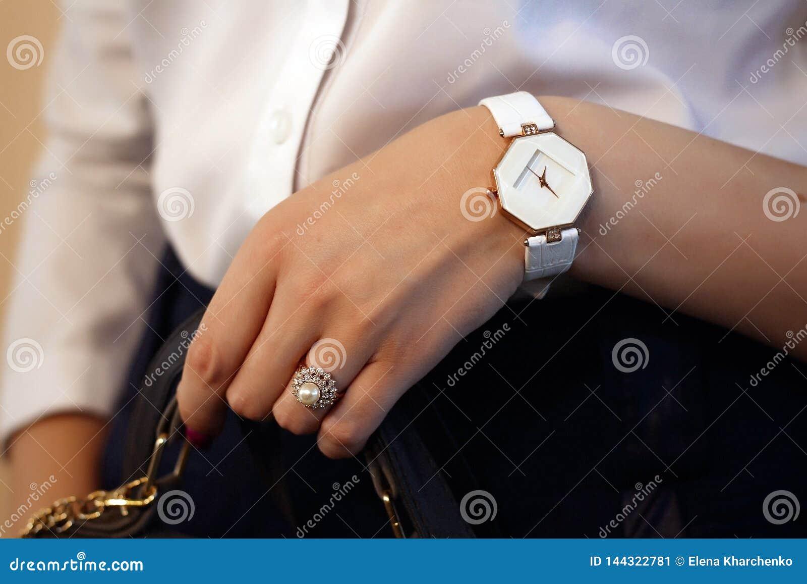 Ένα δαχτυλίδι με τις πέτρες και ένα ρολόι σε ετοιμότητα ενός κοριτσιού