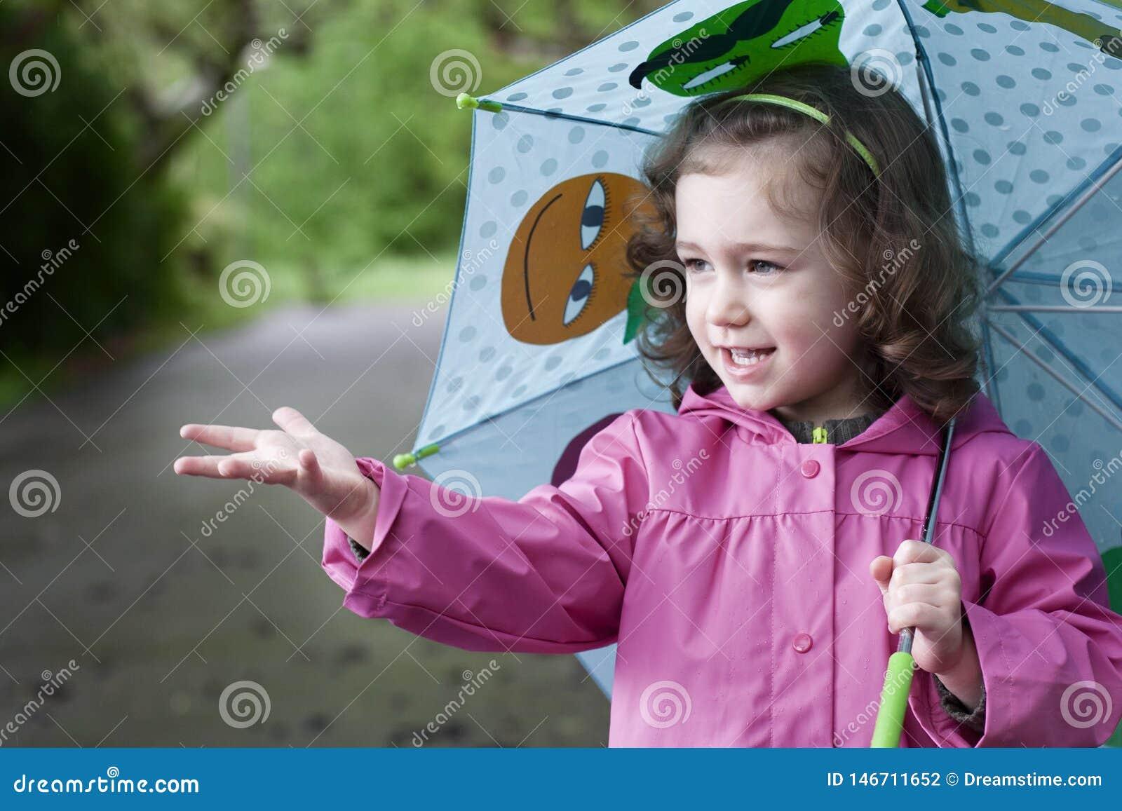 Ένα ευτυχές μικρό κορίτσι σε μια βροχερή ημέρα
