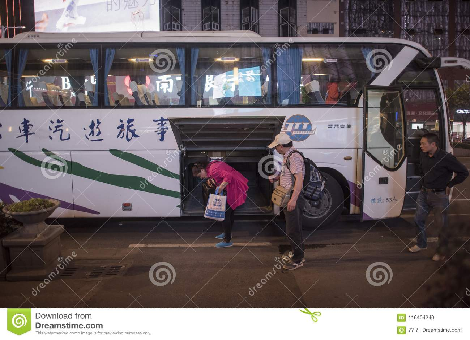Ένα ζευγάρι του μέσης ηλικίας ζεύγους τουριστών που επιστρέφει από το λεωφορείο για να πάρει τις αποσκευές τους, άποψη νύχτας