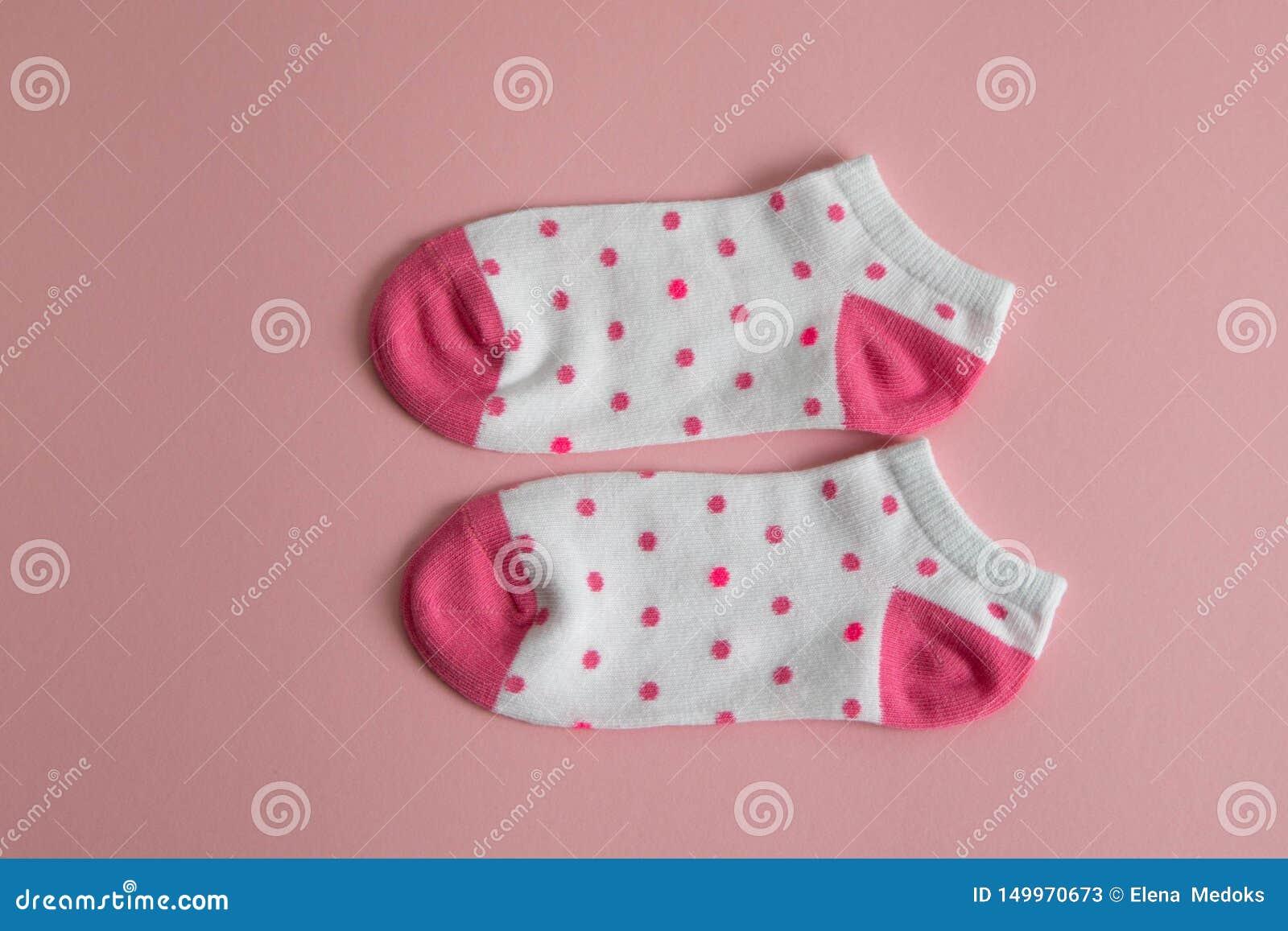 Ένα ζευγάρι των άσπρων καλτσών για τα παιδιά με τις ρόδινες κάλτσες και των τακουνιών, με τα ρόδινα σημεία, σε ένα ρόδινο υπόβαθρ