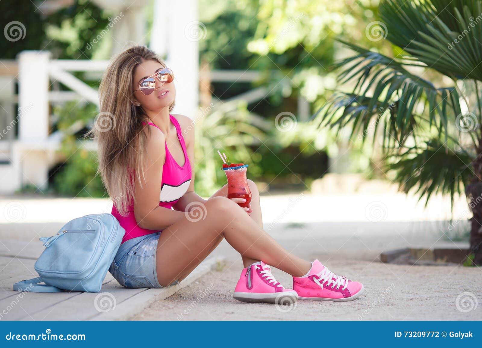 Ένα ζωηρό πορτρέτο της νέας όμορφης γυναίκας με το κοκτέιλ