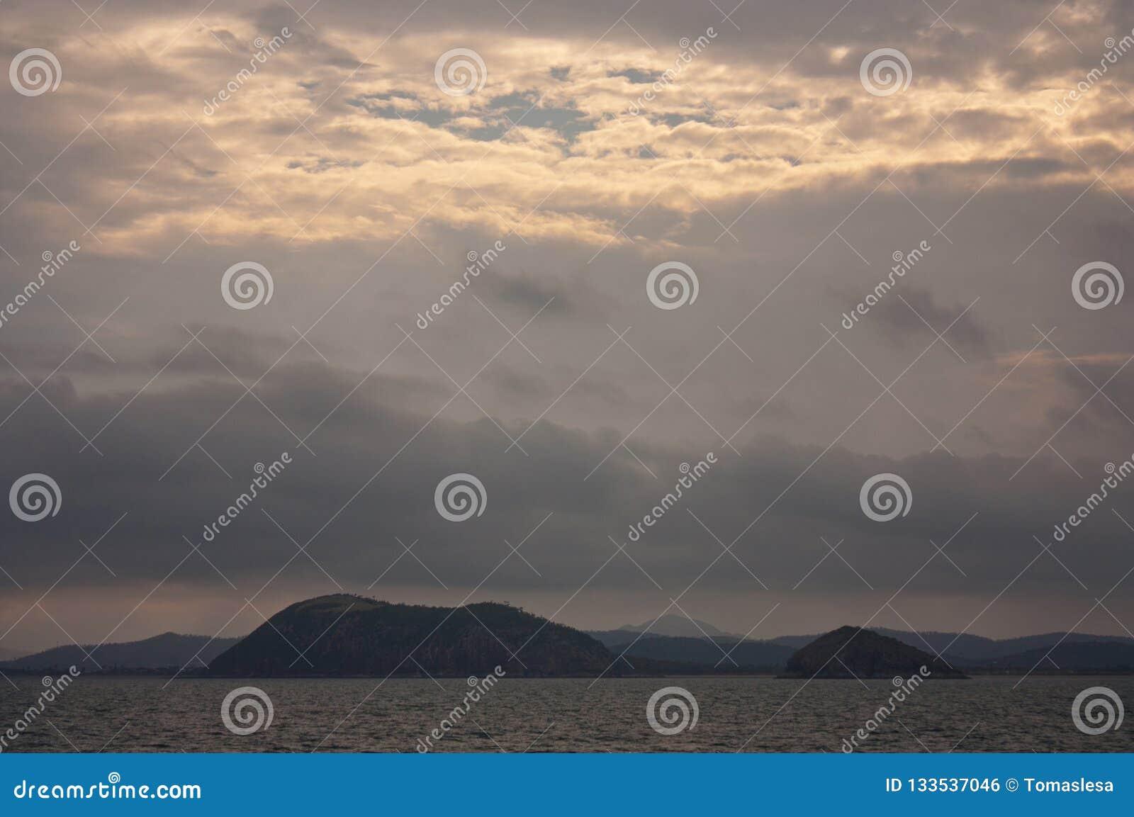 Ένα ηλιοβασίλεμα στη θάλασσα στη μαρίνα κόλπων του Ρόσλυν κοντά σε Yeppoon στον τροπικό κύκλο της περιοχής Αιγοκέρου στο κεντρικό