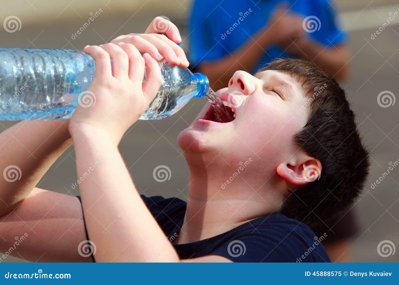 Ένα διψασμένο ανυπόμονα πόσιμο νερό αγοριών