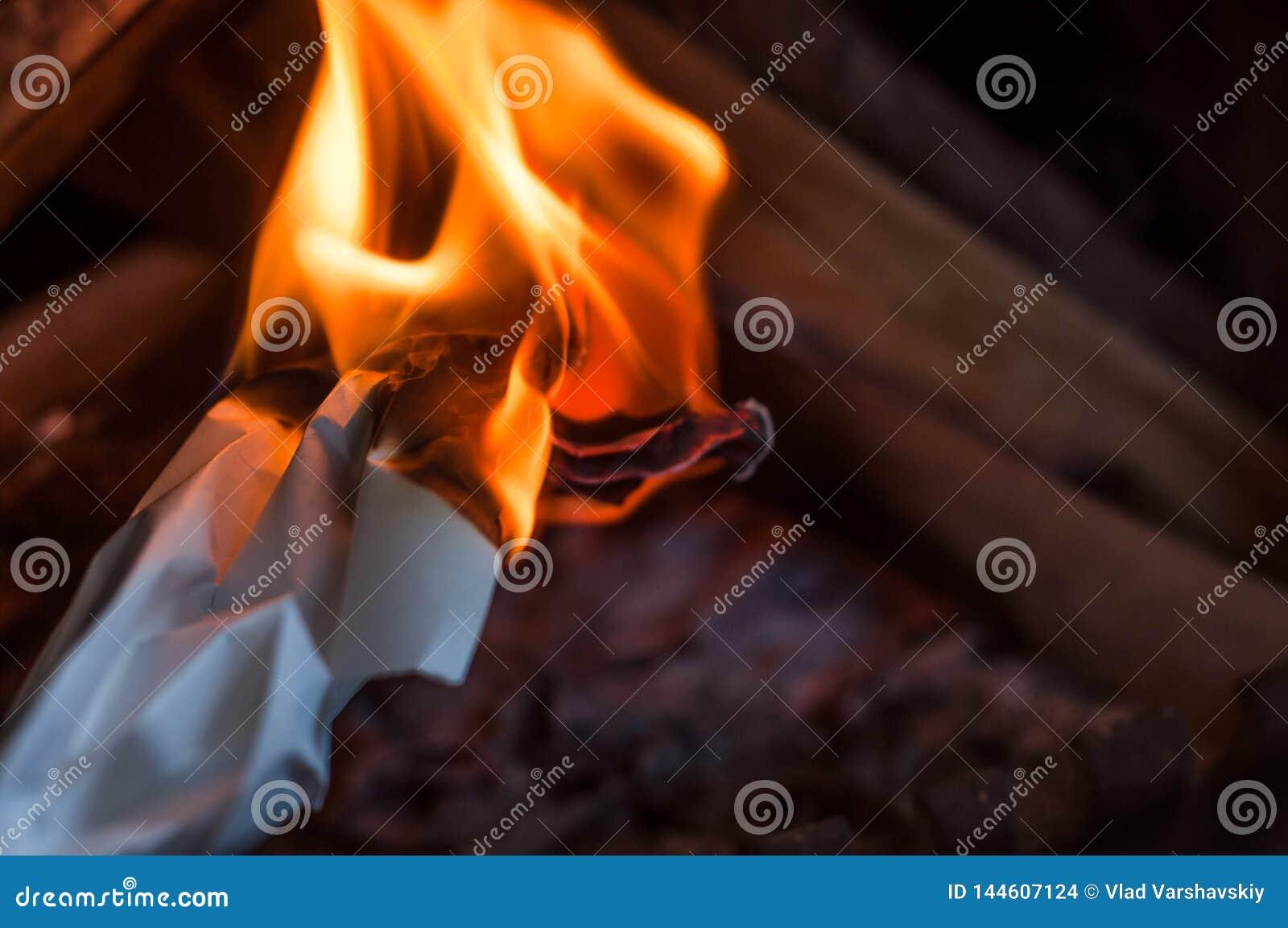 Ένα κάψιμο φύλλων του εγγράφου με μια κόκκινη πορτοκαλιά φωτεινή φλόγα με τη θερμότητα