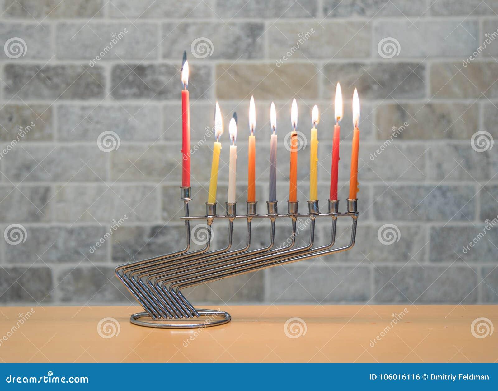 Ένα κηροπήγιο μετάλλων για τον εορτασμό Hanukkah στέκεται με τα αναμμένα κεριά στον πίνακα ενάντια στο σκηνικό ενός τουβλότοιχος