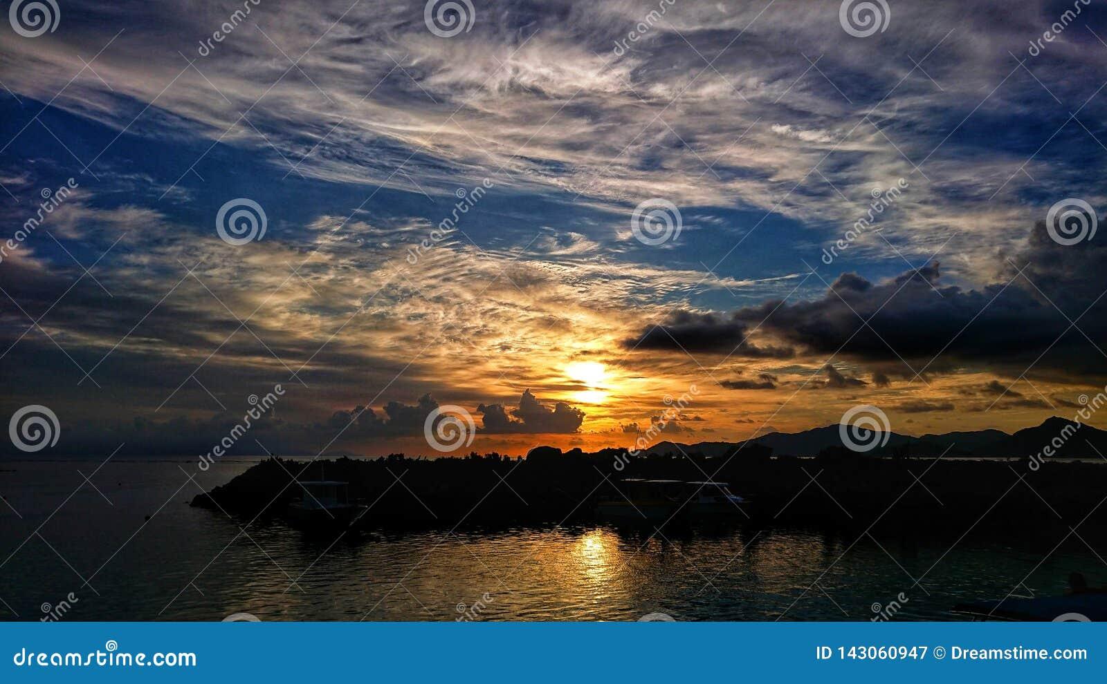 Ένα κομμάτι του κέικ σύννεφων στο ηλιοβασίλεμα Λα Digue Σεϋχέλλες θέσης