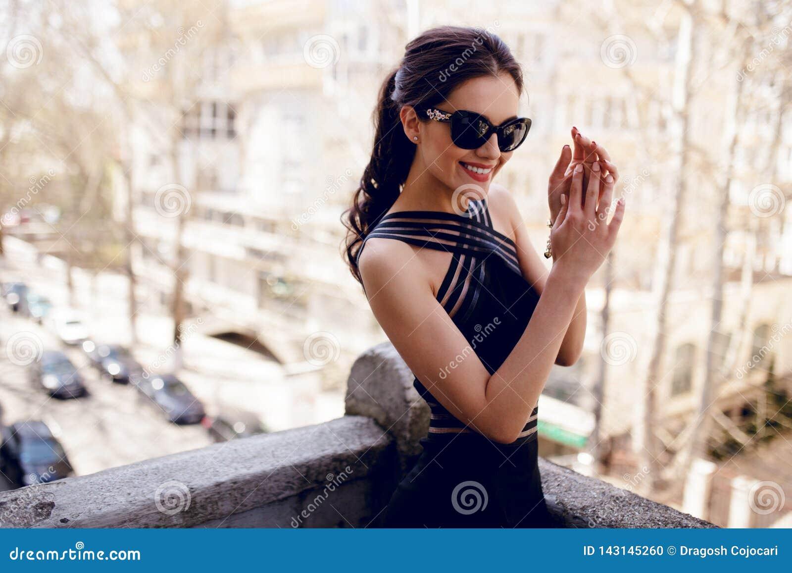 Ένα κομψό, κομψό brunette στα μαύρα γυαλιά ηλίου, προκλητικό μαύρο φόρεμα, τρίχα ponytail, χαμογελά με τα χέρια κοντά στο πρόσωπο