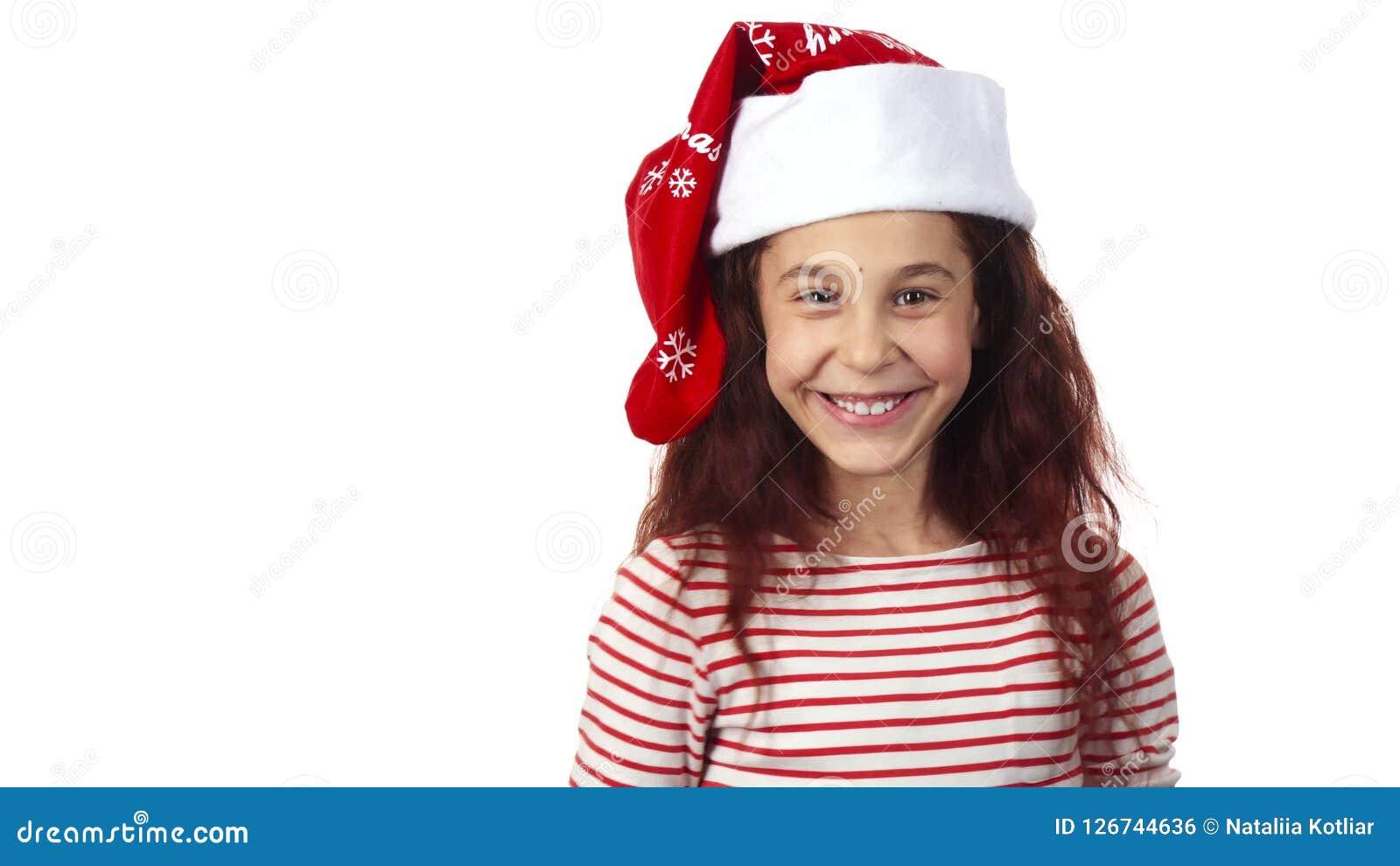 Ένα κορίτσι σε έναν Άγιο Βασίλη ΚΑΠ χαμογελά στη κάμερα