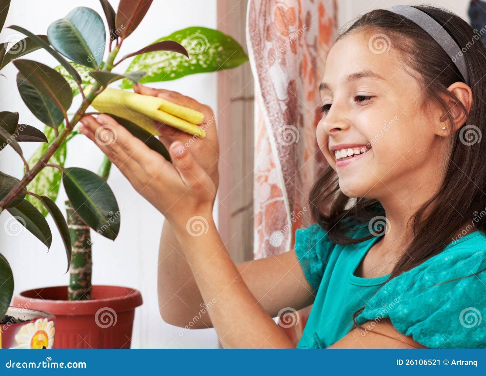 Ένα κορίτσι σκουπίζει τη σκόνη από τα φύλλα