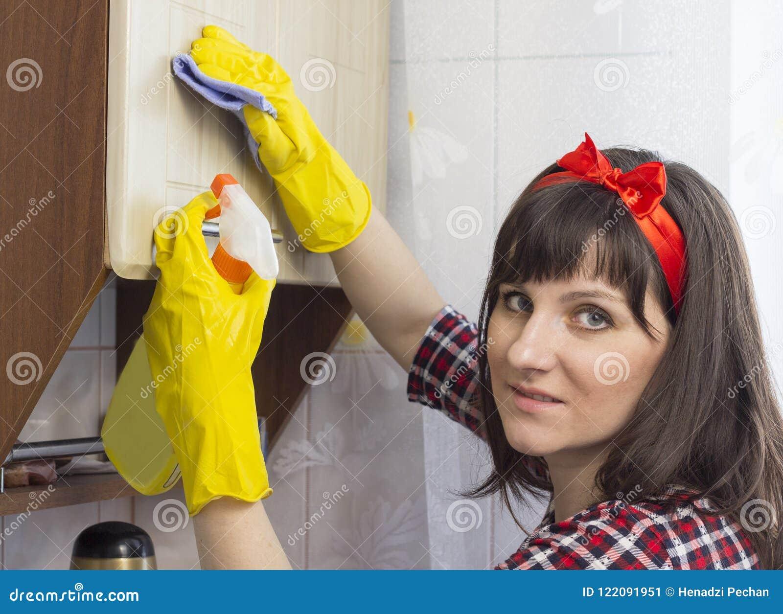 Ένα κορίτσι στα κίτρινα γάντια πλένει το ντουλάπι στην κουζίνα, συσκευή κινηματογραφήσεων σε πρώτο πλάνο