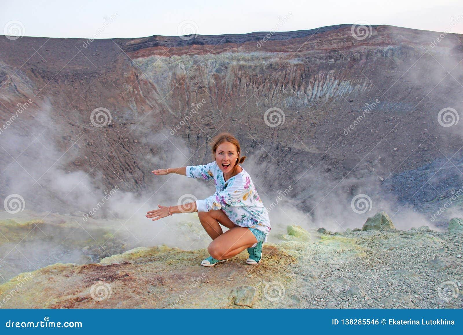 Ένα κορίτσι στο γκρίζο ηφαίστειο υδρογόνου και το ηφαίστειο φτιάχνει κρατήρα σε Vulca