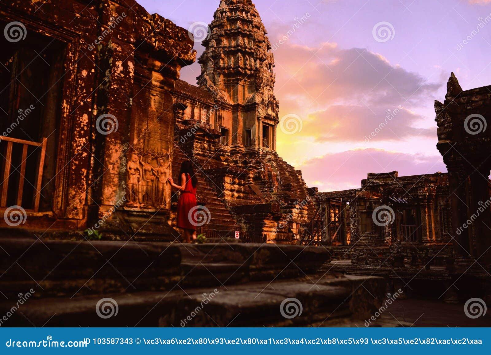 Ένα κόκκινο κορίτσι φορεμάτων που κοιτάζει επίμονα στο αρχαίο Angkor Wat