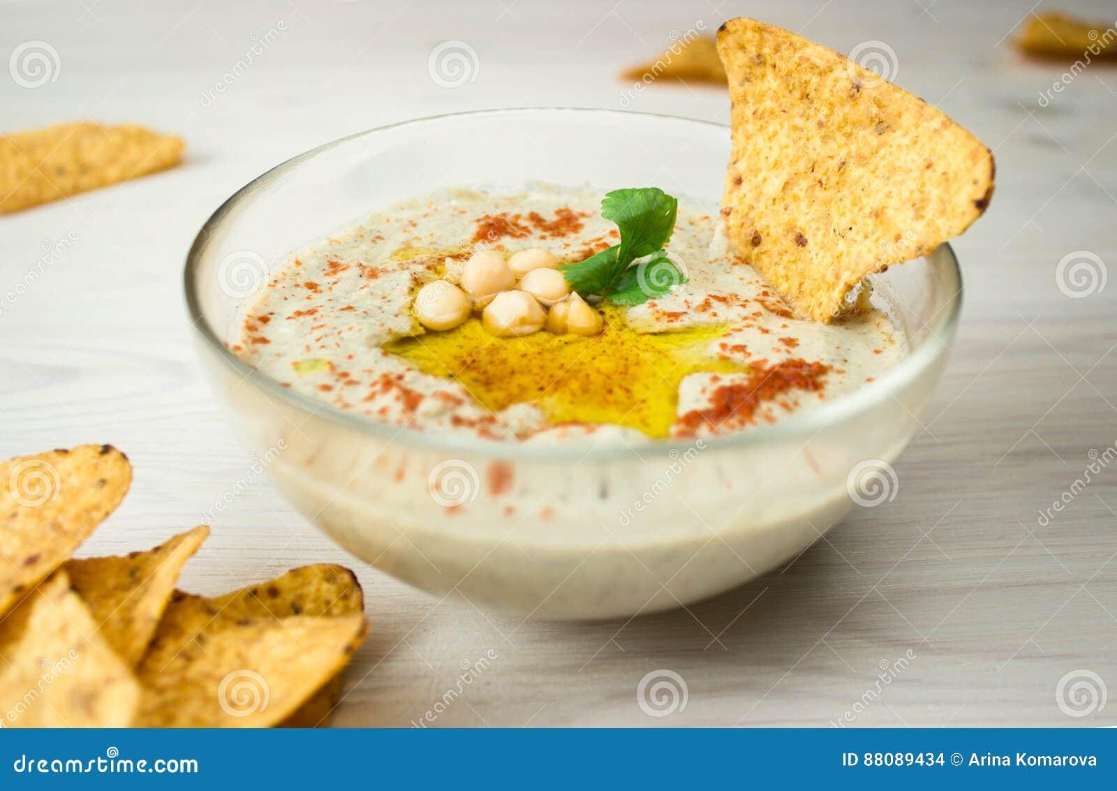 Ένα κύπελλο του κρεμώδους hummus με το ελαιόλαδο και τα τσιπ