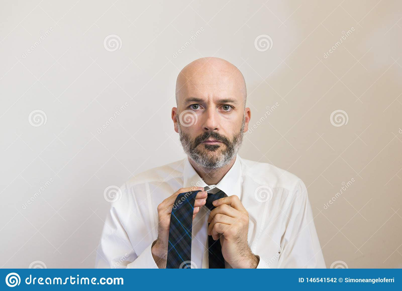 Ένα μέσο άτομο ηλικίας με τη γενειάδα δένει τη γραβάτα του