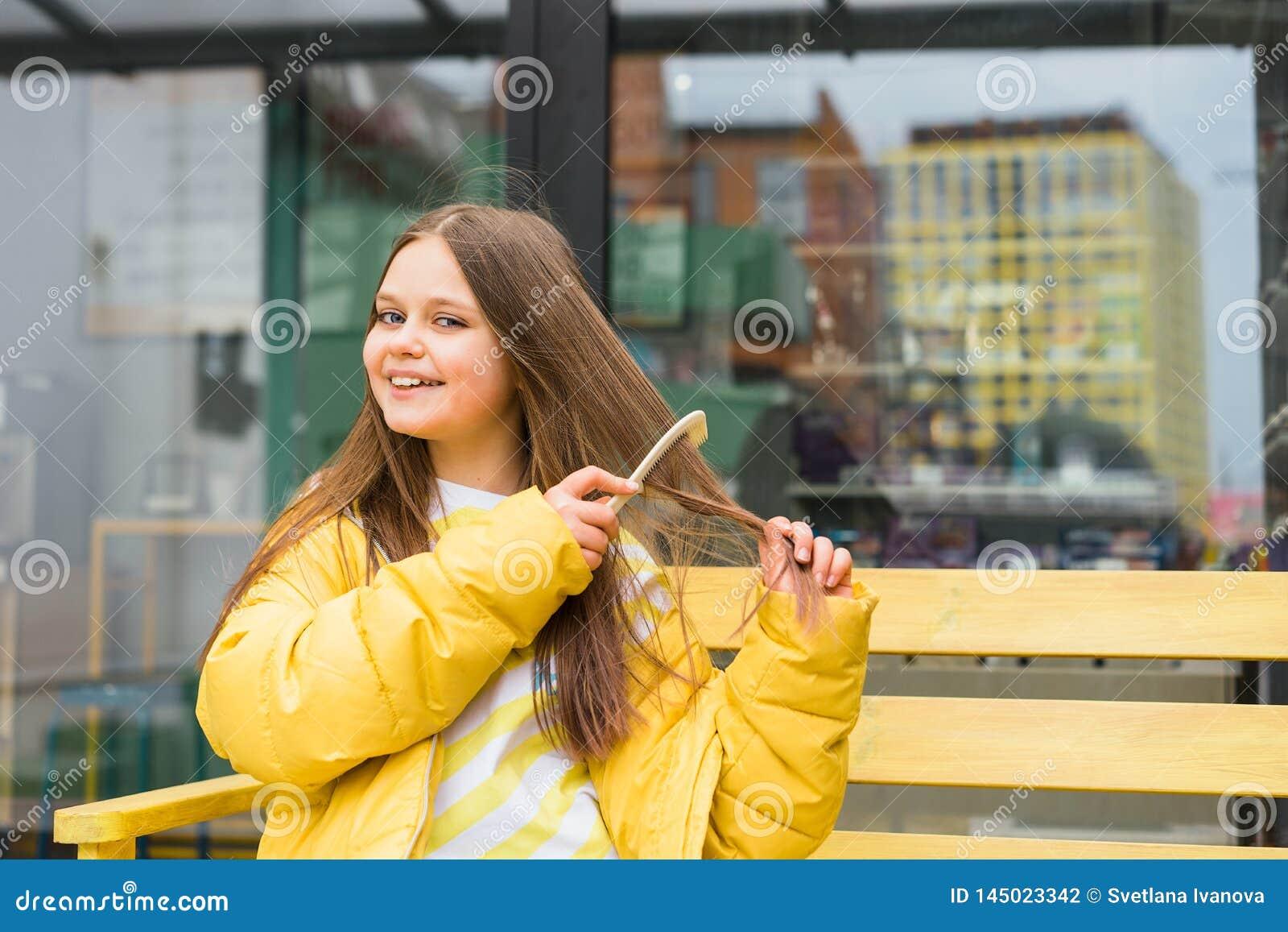 Ένα μακρυμάλλες, εύθυμο ξανθό κορίτσι κτενίζει την τρίχα της