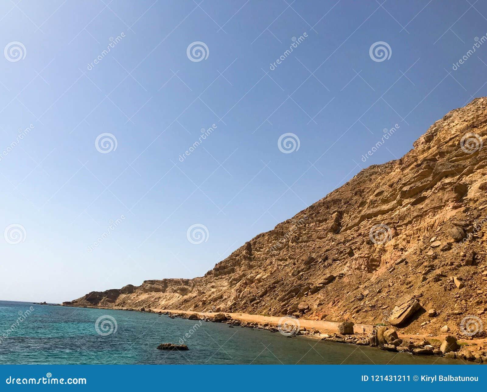 Ένα μεγάλο όμορφο μεγαλοπρεπές αμμώδες βουνό πετρών, ένα ανάχωμα, ένας λόφος, ένας λόφος στην έρημο ενάντια στο μπλε ουρανό και α