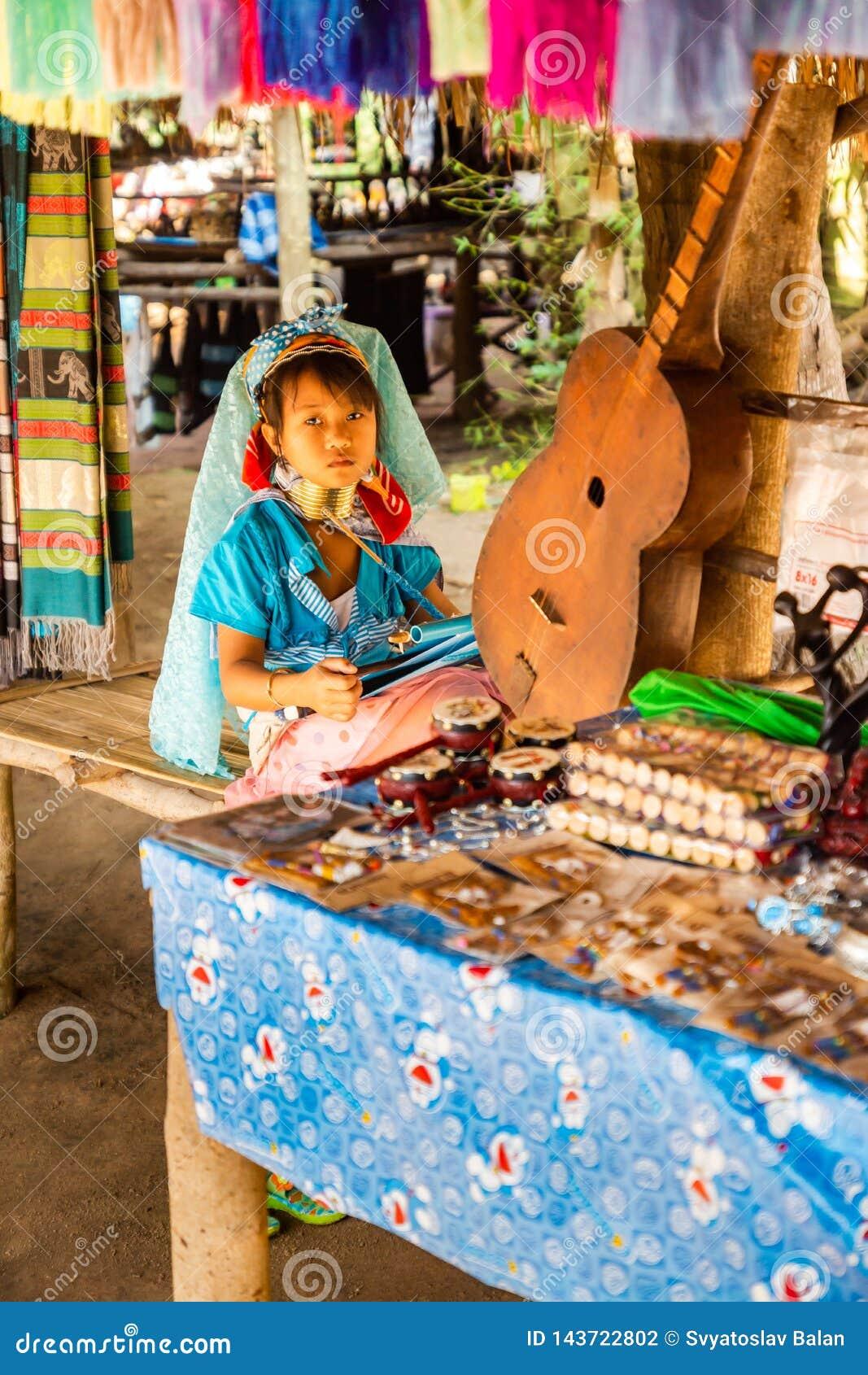 Ένα μικρό κορίτσι με έναν μακρύ λαιμό και δαχτυλίδια σε την που κάνει το μετάξι στο μακρύ χωριό λαιμών