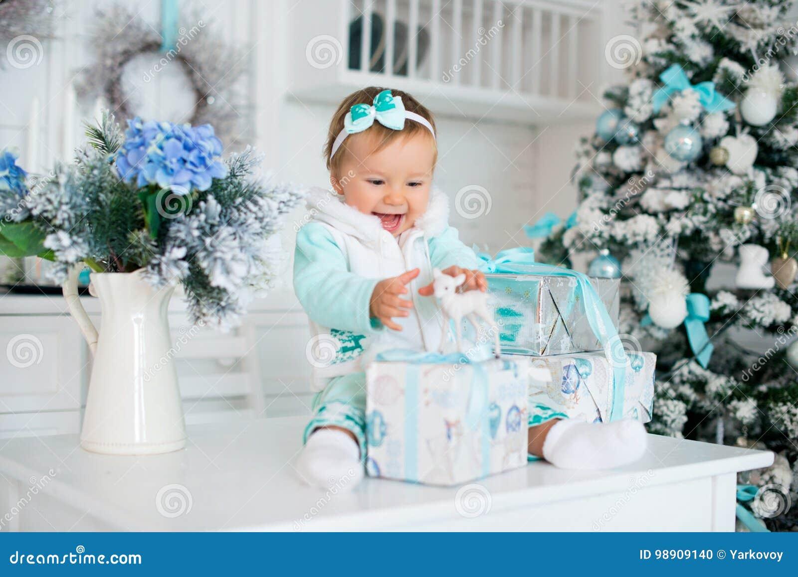Ένα μικρό κορίτσι με τα δώρα και ένα ελάφι παιχνιδιών Διακοπές Χριστουγέννων