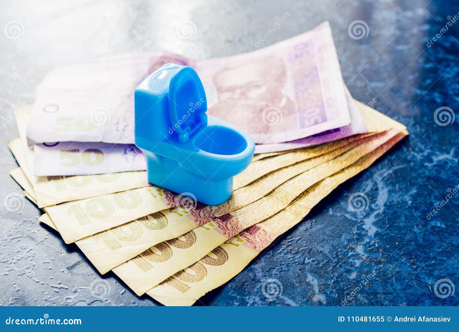 Ένα μπλε κύπελλο τουαλετών παιχνιδιών στέκεται στα χρήματα των ουκρανικών hryvnas