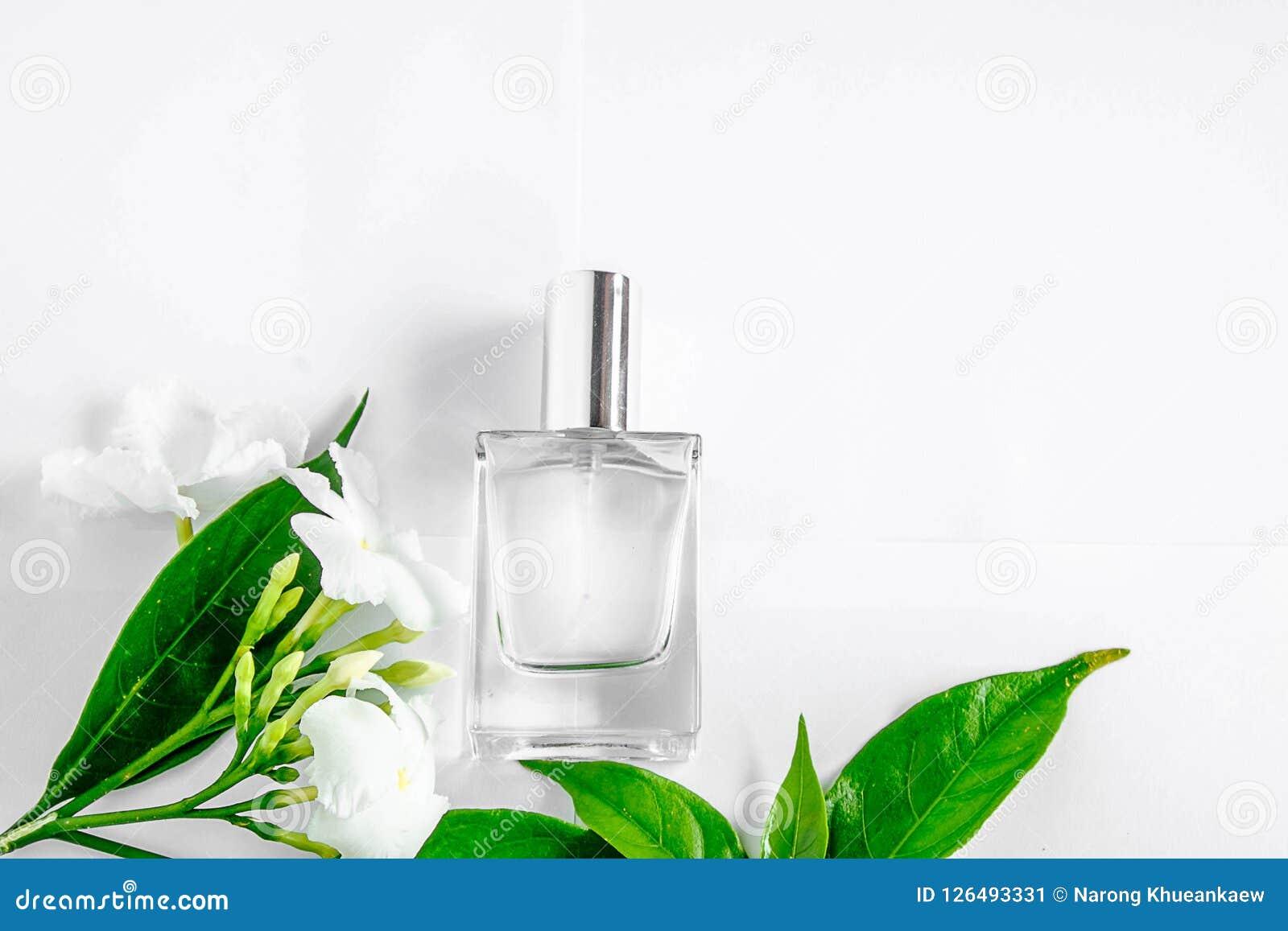 Ένα μπουκάλι του άσπρων αρώματος και των λουλουδιών με τα φύλλα