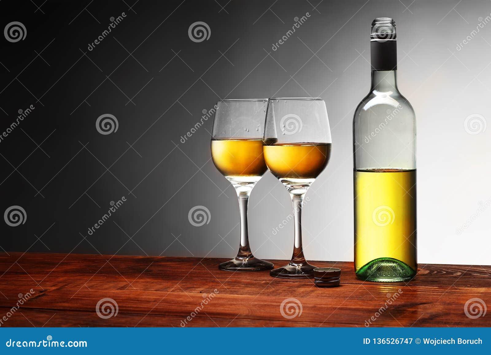 Ένα μπουκάλι του κρασιού με δύο πλήρη goblets