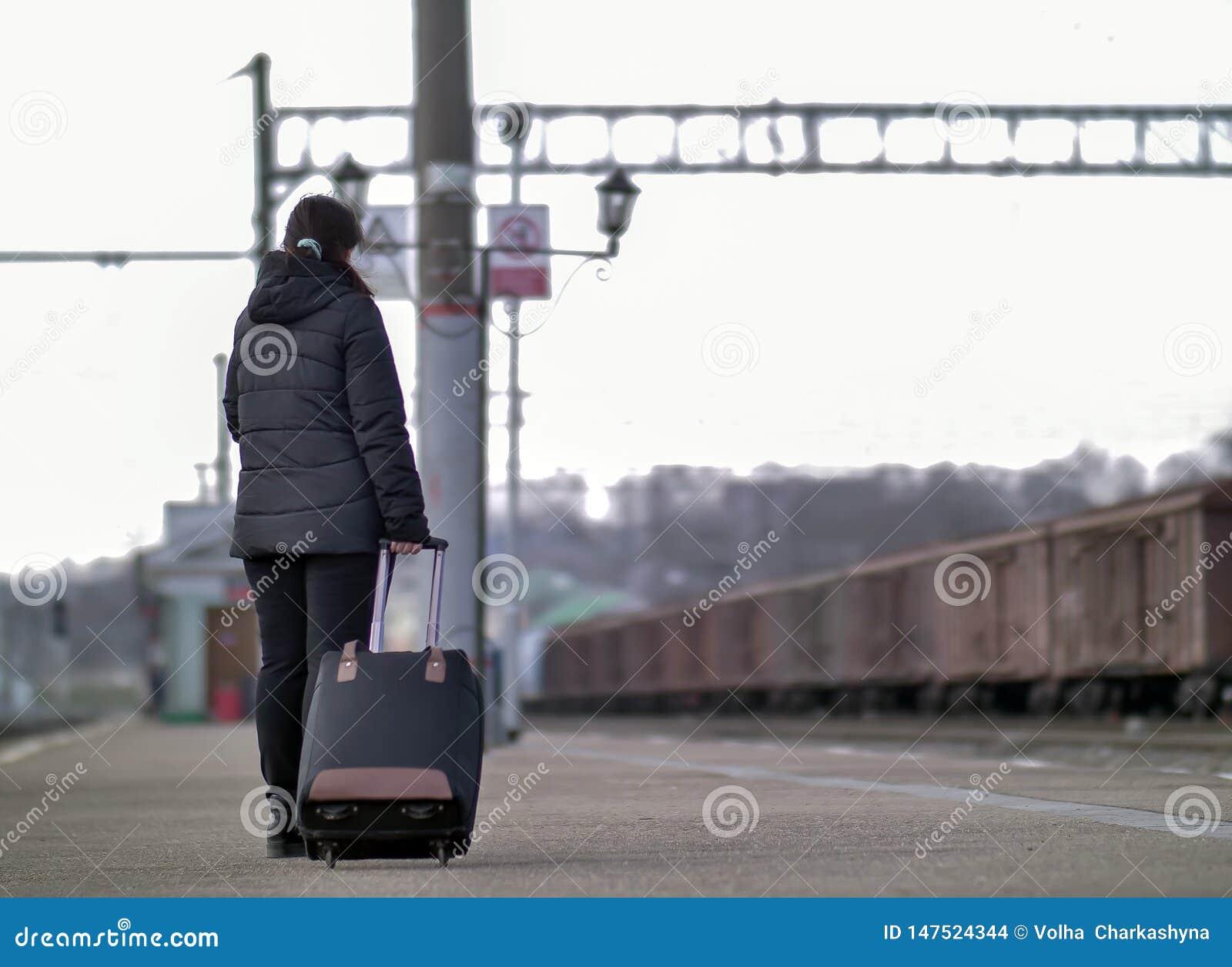 Ένα μόνο κορίτσι με μια μαύρη βαλίτσα στέκεται στην πλατφόρμα περιμένοντας το τραίνο