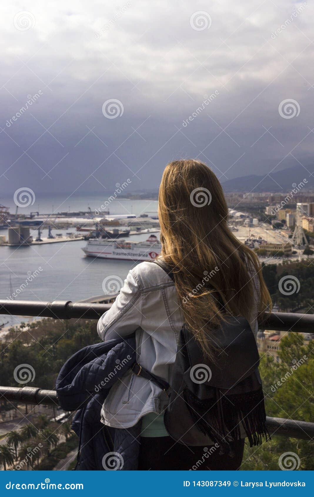 Ένα μόνο κορίτσι στέκεται σε έναν λόφο και εξετάζει το όμορφο πανόραμα της ισπανικής πόλης της Μάλαγας μια θερμή ηλιόλουστη ημέρα