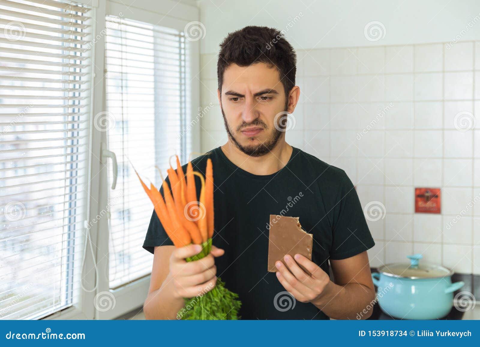 Ένα νέο άτομο brunette εξετάζει ένα καρότο με την περιφρόνηση και την αποστροφή