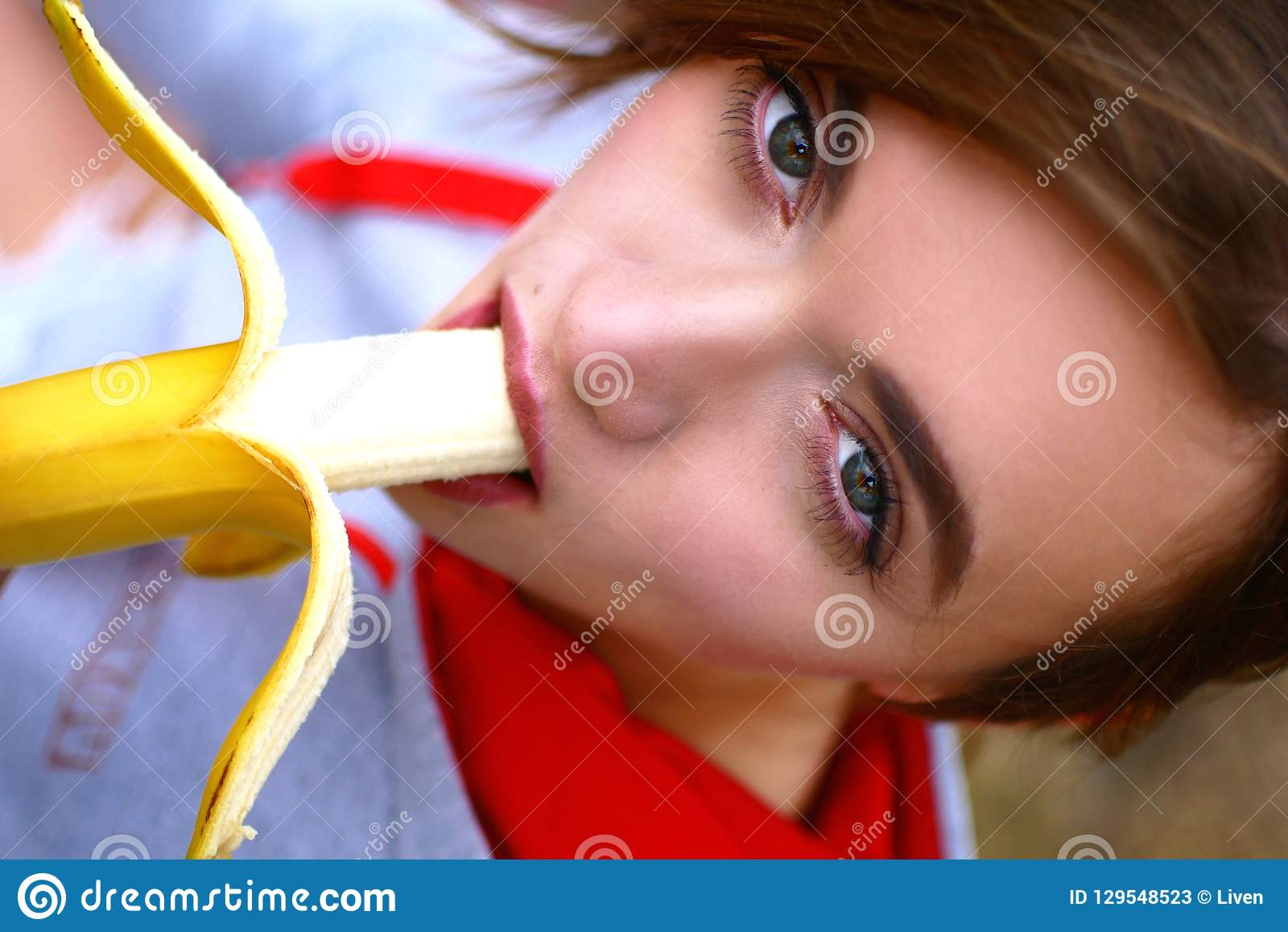 Ένα νέο γλυκό κορίτσι είναι πολύ σαγηνευτικό τρώγοντας μια μπανάνα Μια αθλήτρια προσέχει τα τρόφιμά της