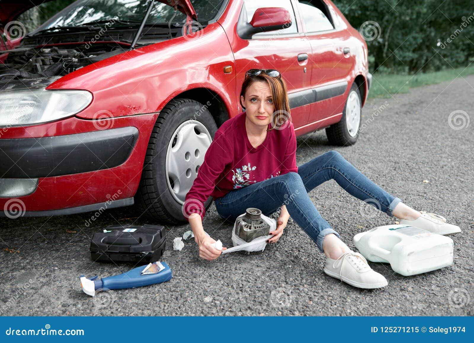 Ένα νέο κορίτσι κάθεται κοντά σε ένα σπασμένο αυτοκίνητο και κάνει τις επισκευές στην ηλεκτρική γεννήτρια, δίπλα σε την υπάρχουν