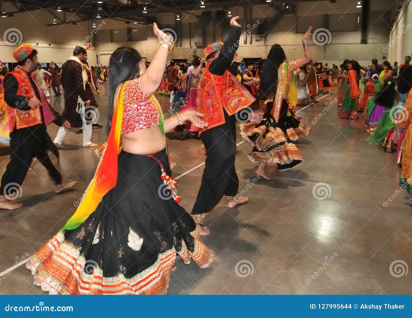 Ένα νέο κορίτσι και μια ομάδα ανθρώπων απολαμβάνουν το ινδό φεστιβάλ της φθοράς Navratri Garba παραδοσιακής καταναλώνουν