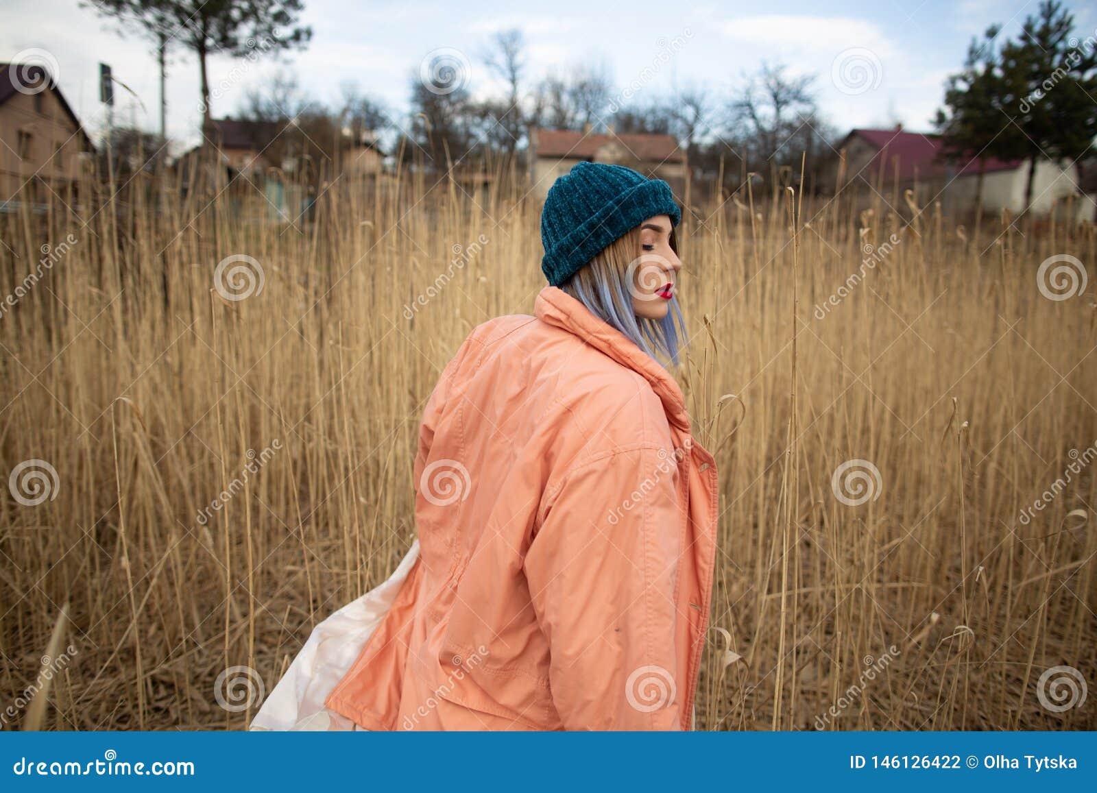 Ένα νέο κορίτσι που φορά ένα παλτό κρητιδογραφιών και ένα μοντέρνο καπέλο θέτει σε έναν τομέα σίτου Πλάτη viev