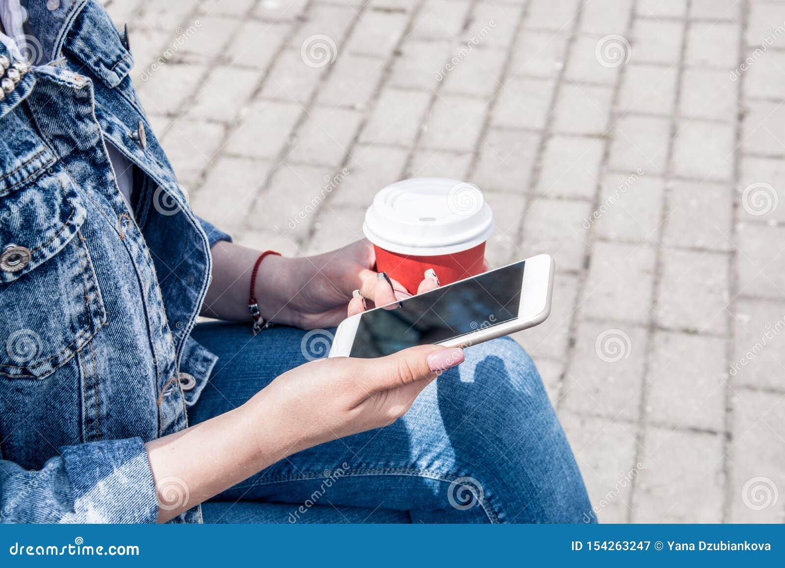 Ένα νέο κορίτσι σε ένα σακάκι τζιν περπατά κάτω από την οδό με τον καφέ και ένα τηλέφωνο στα χέρια της Κορίτσι στα γυαλιά και ένα