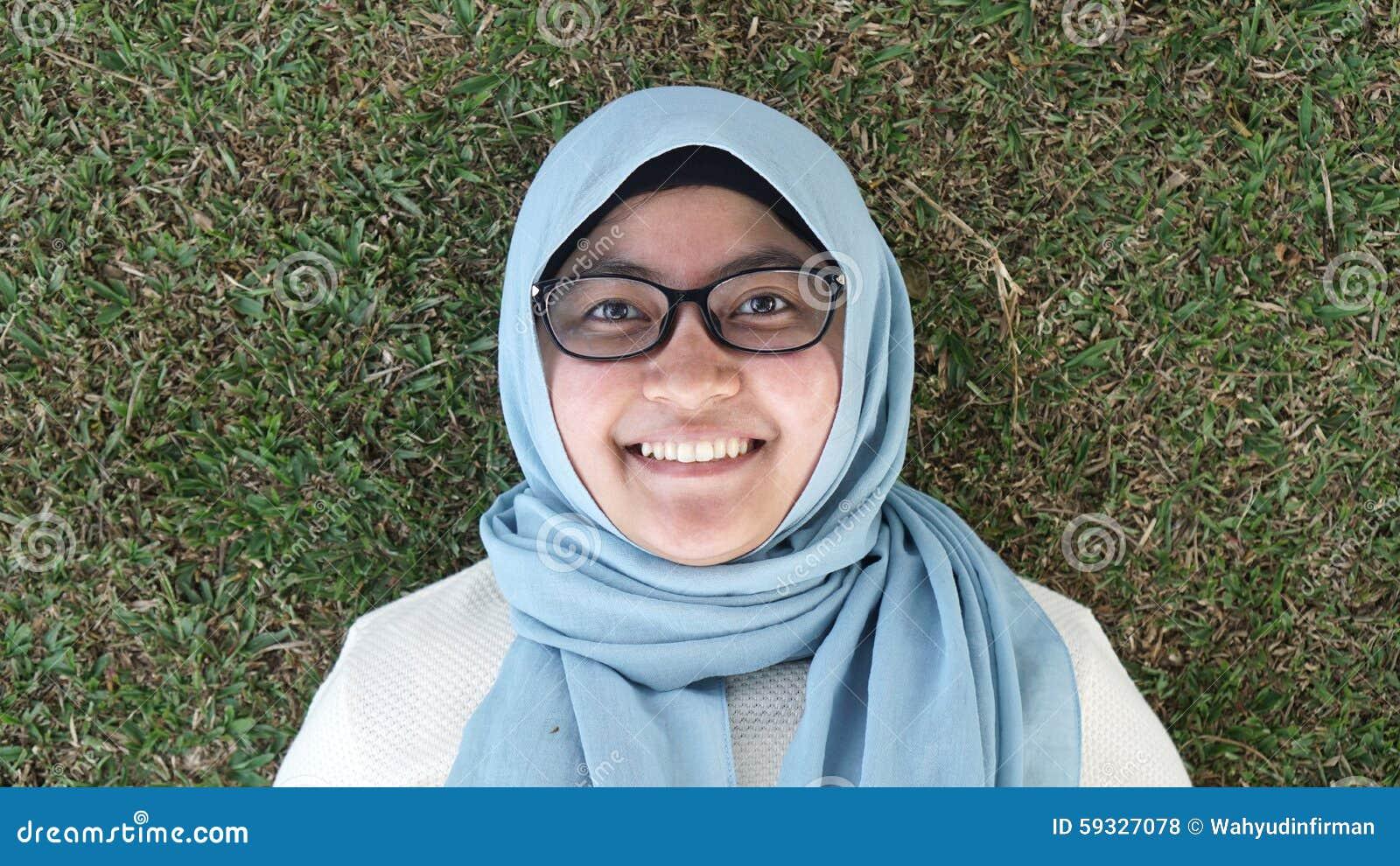 Ένα νέο μουσουλμανικό κορίτσι που βάζει στην πράσινη χλόη