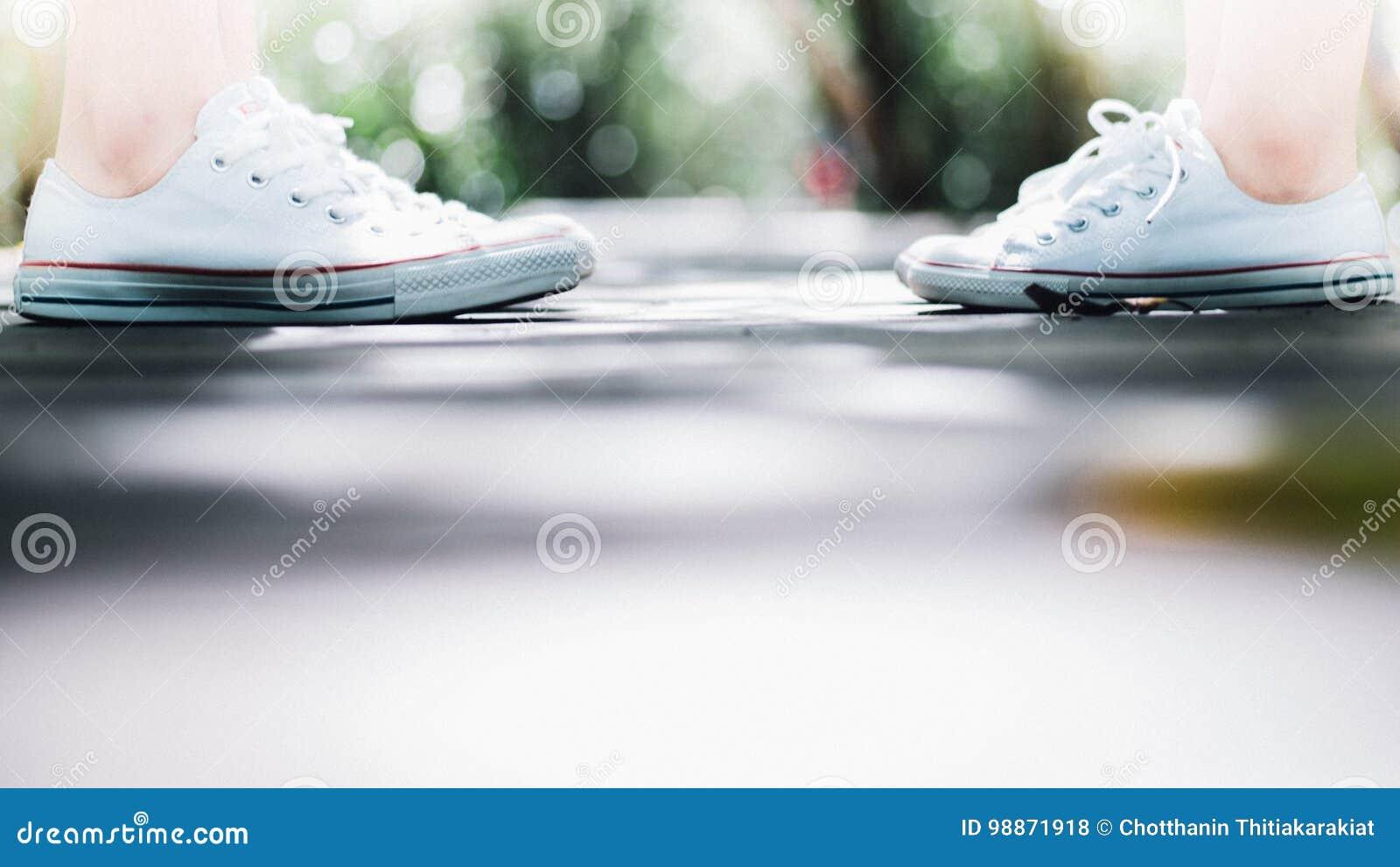 Ένα πάνινο παπούτσι ένδυσης ζευγών που στέκεται αντιμετωπίζει το ένα το άλλο κατά μήκος του τρόπου περιπάτων, έννοια αγάπης