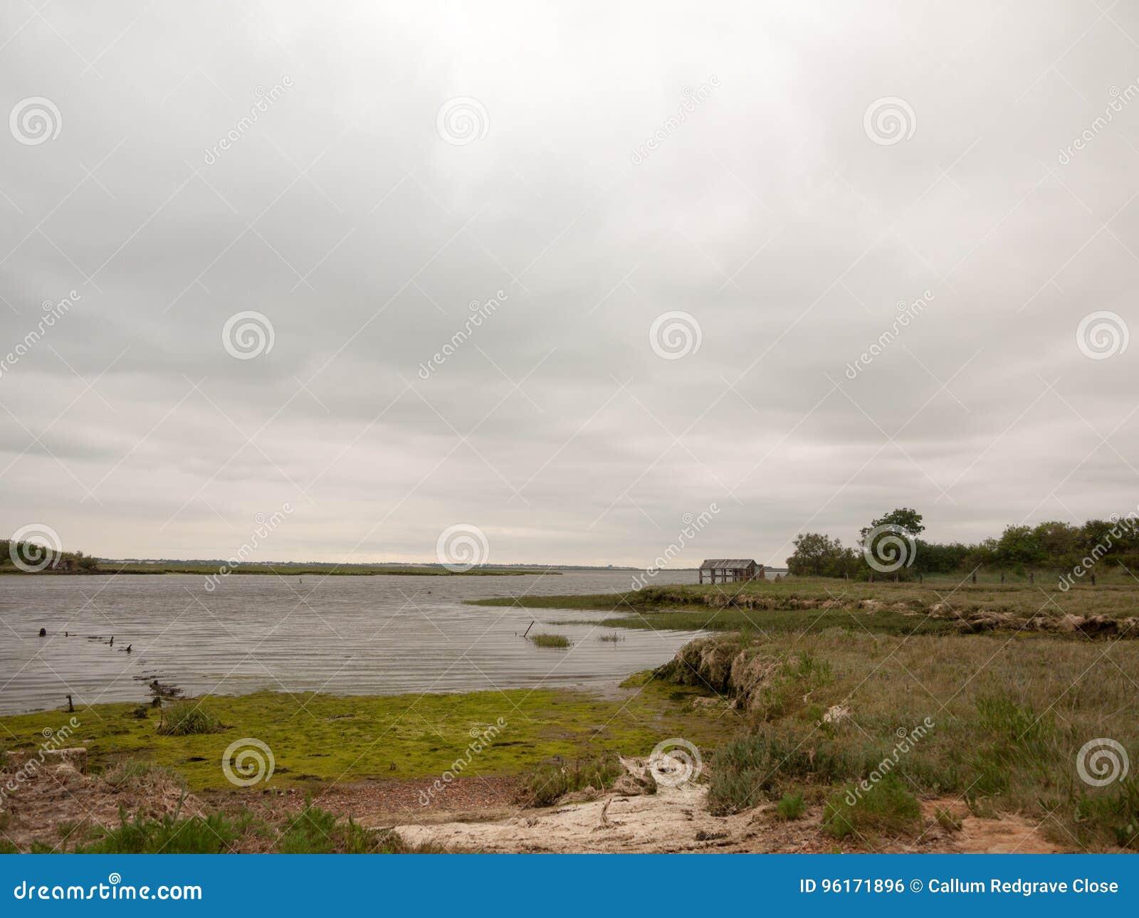 Ένα παράκτιο συννεφιασμένος θάλασσας τοπίων και κενός