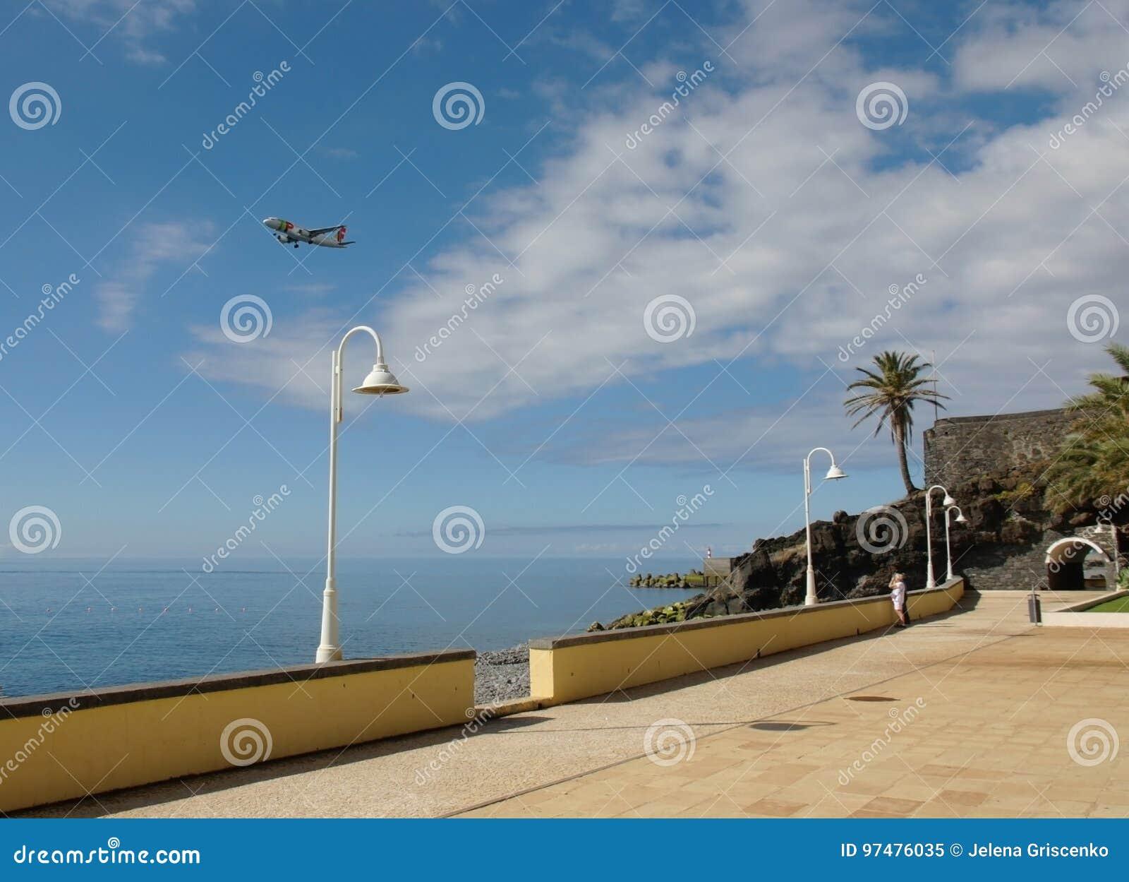 Ένα πετώντας αεροπλάνο στον ουρανό και όμορφο seascape της Μαδέρας