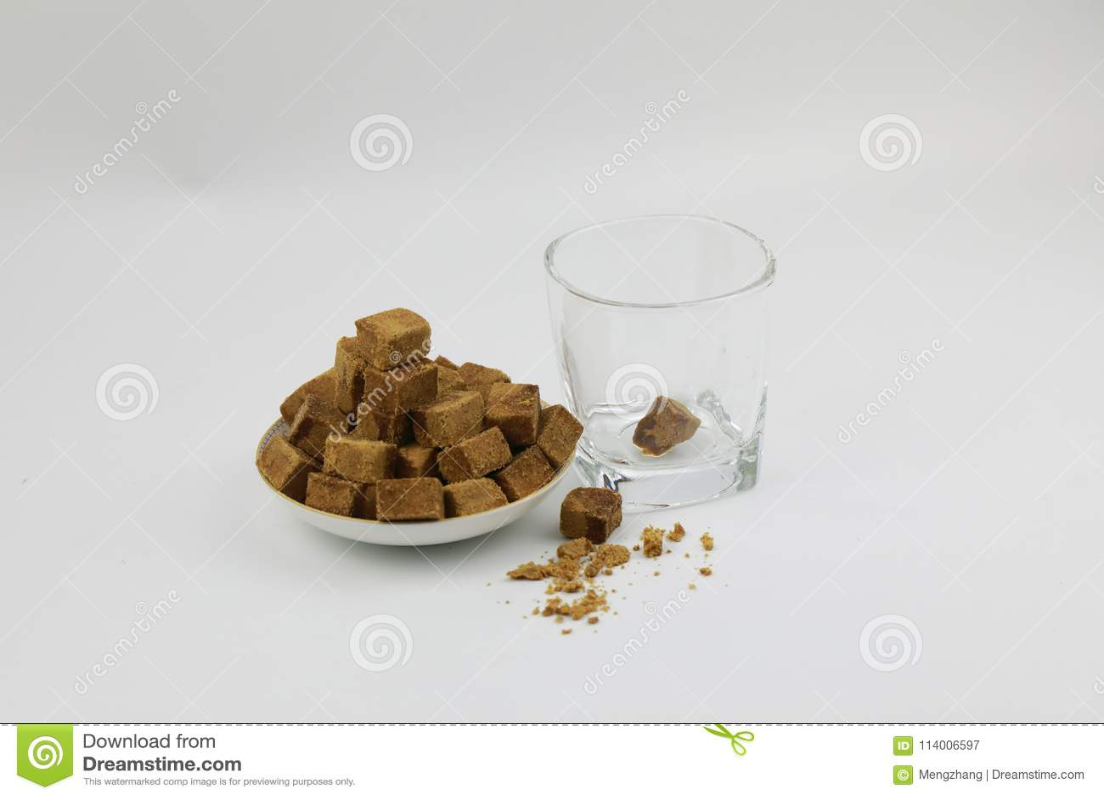 Ένα πιάτο της καφετιάς ζάχαρης κυβίζει τη ζάχαρη βράχου, διαφανές γυαλί Α εκτός από, ένα κομμάτι της καφετιάς ζάχαρης στο ποτήρι