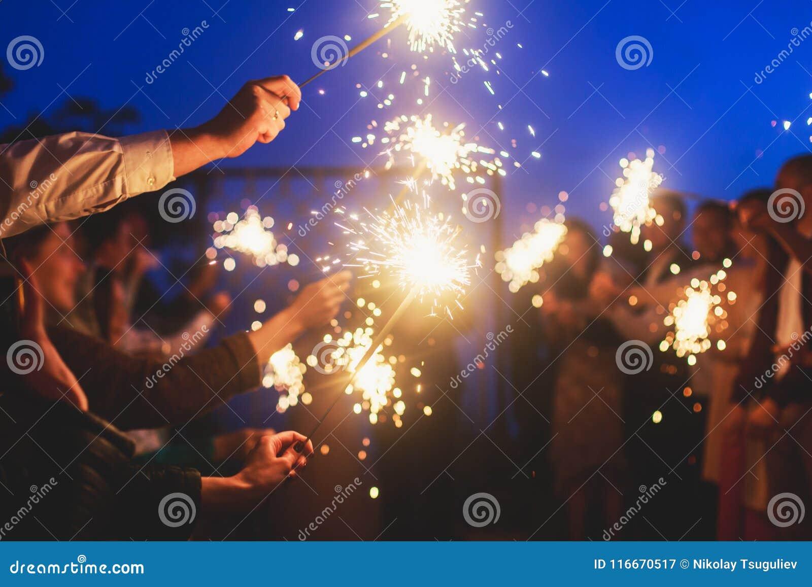 Ένα πλήθος των ευτυχών νέων με τα sparklers πυρκαγιάς της Βεγγάλης στα χέρια τους κατά τη διάρκεια του εορτασμού γενεθλίων