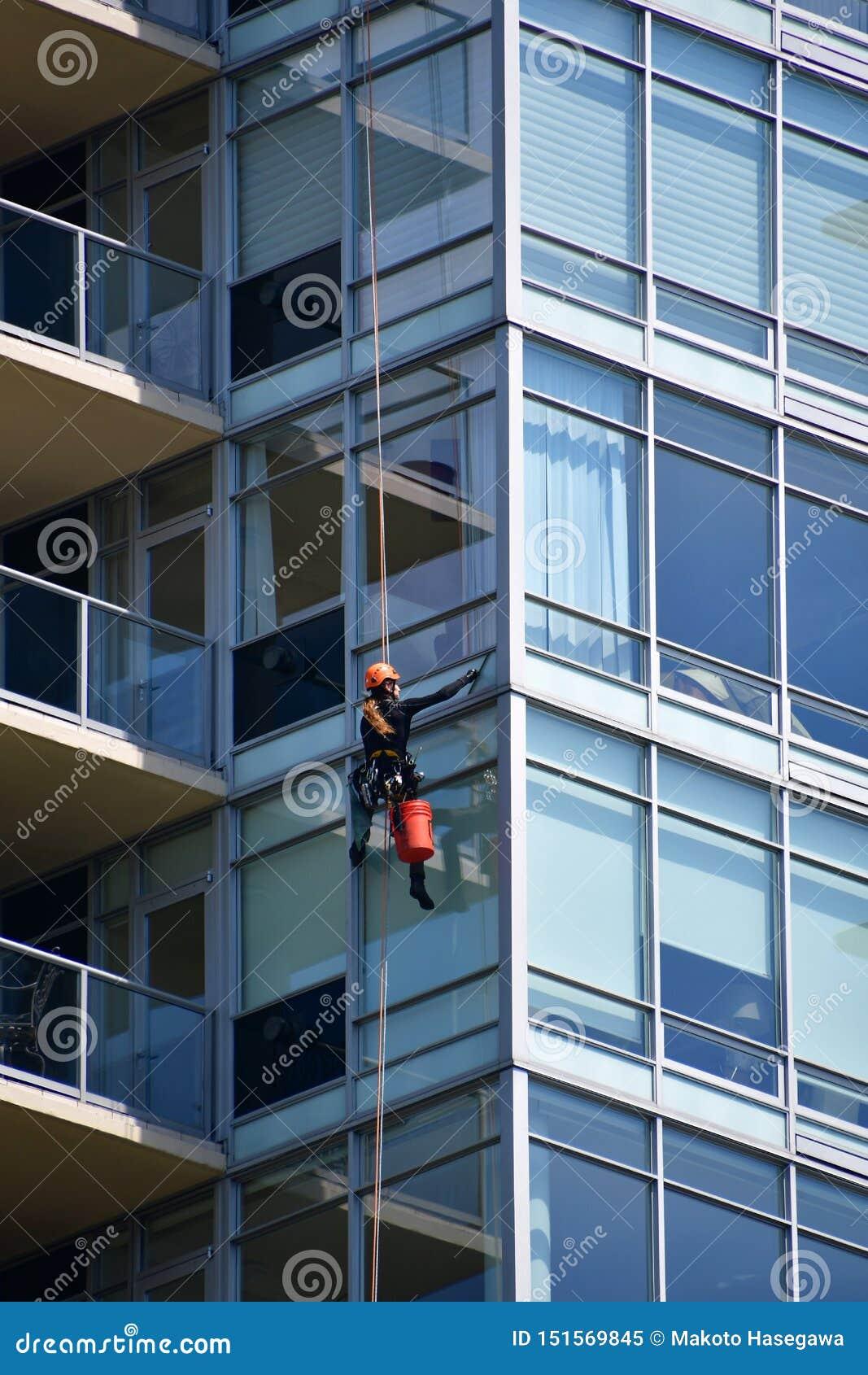 Ένα πλυντήριο παραθύρων που καθαρίζει το παράθυρο ενός υψηλού κτηρίου ανόδου